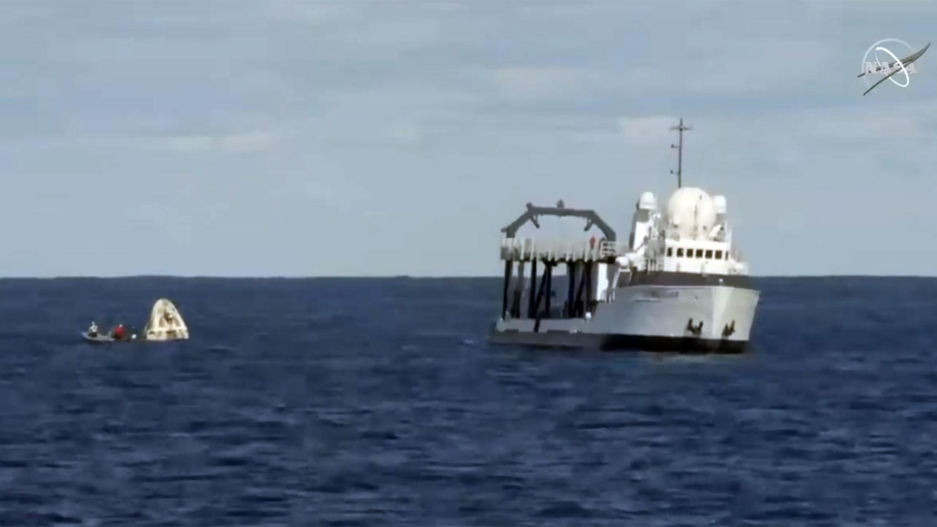 """Los equipos a bordo del buque de rescate """"Go Searcher"""" de SpaceX utilizarán una grúa para sacar a la nave espacial del océano."""