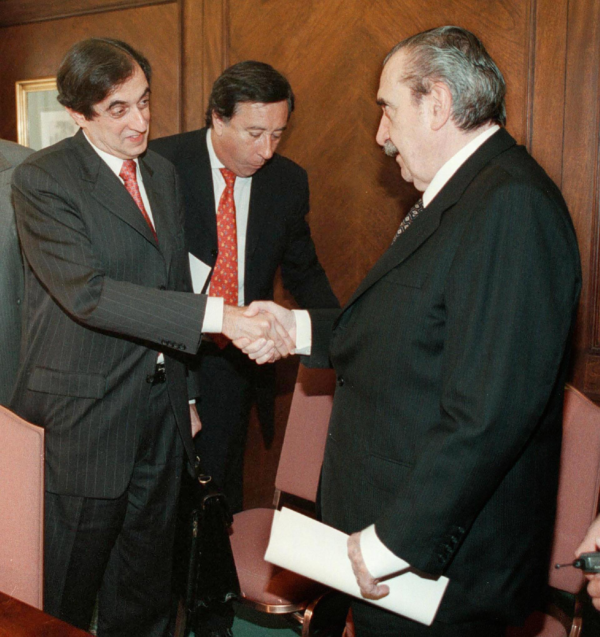 Alfonsín, como senador, le da la manoal representante del Fondo Monetario Internacional, Anoop Singh, luego de una reunión mantenida en un hotel internacional del barrio porteño de Retiro