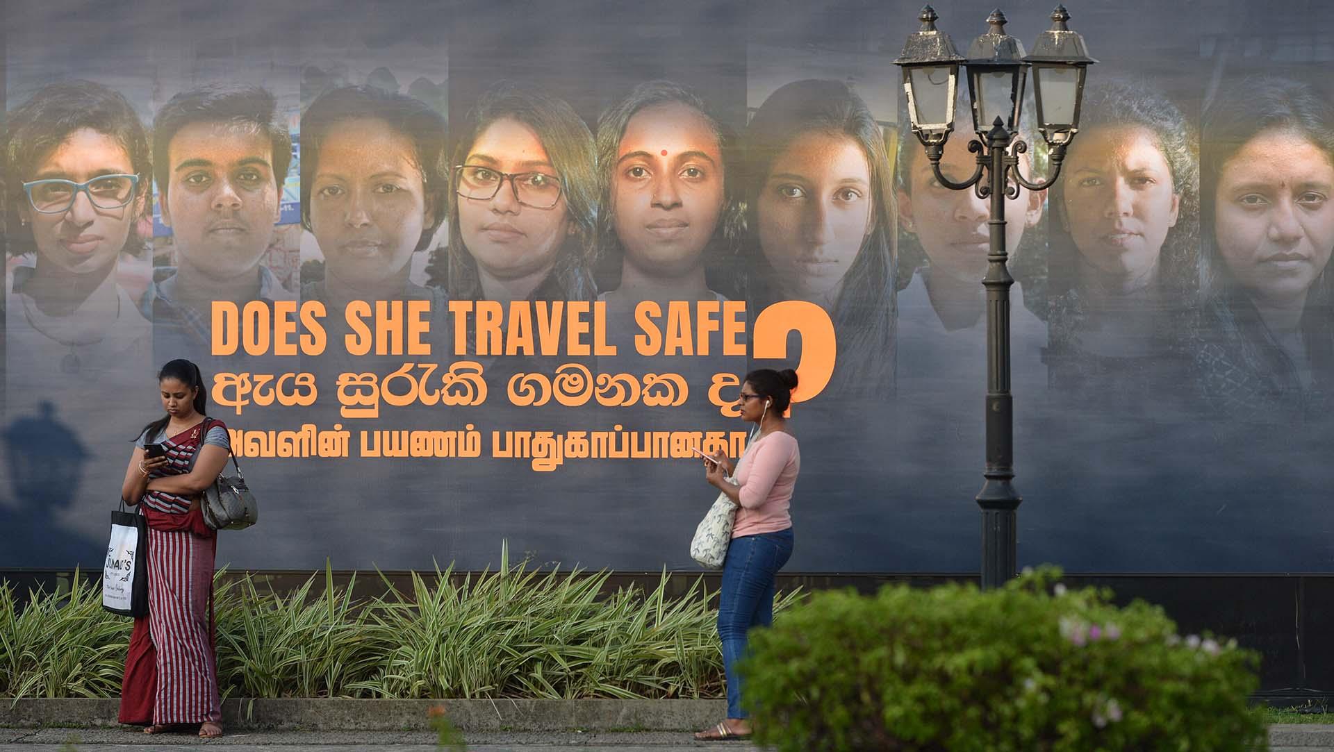 Mujeres ante un cartel por el Día Internacional de la Mujer en Colombo, Sri Lanka (Photo by ISHARA S. KODIKARA / AFP)