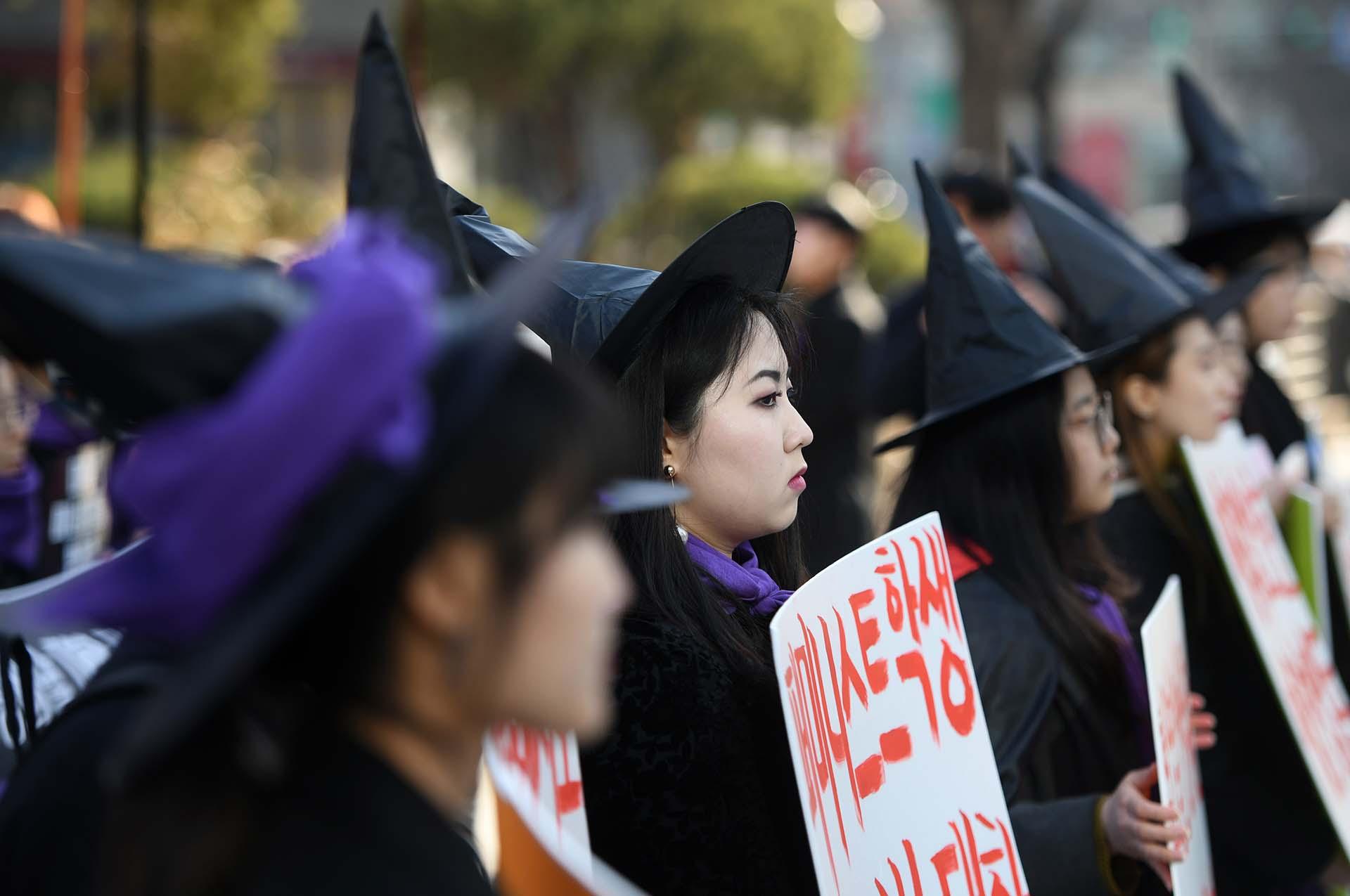 Mujeres surcoreanas vestidas de brujas mientras sostienen pancartas feministas en Seu (Photo by JUNG Yeon-Je / AFP)