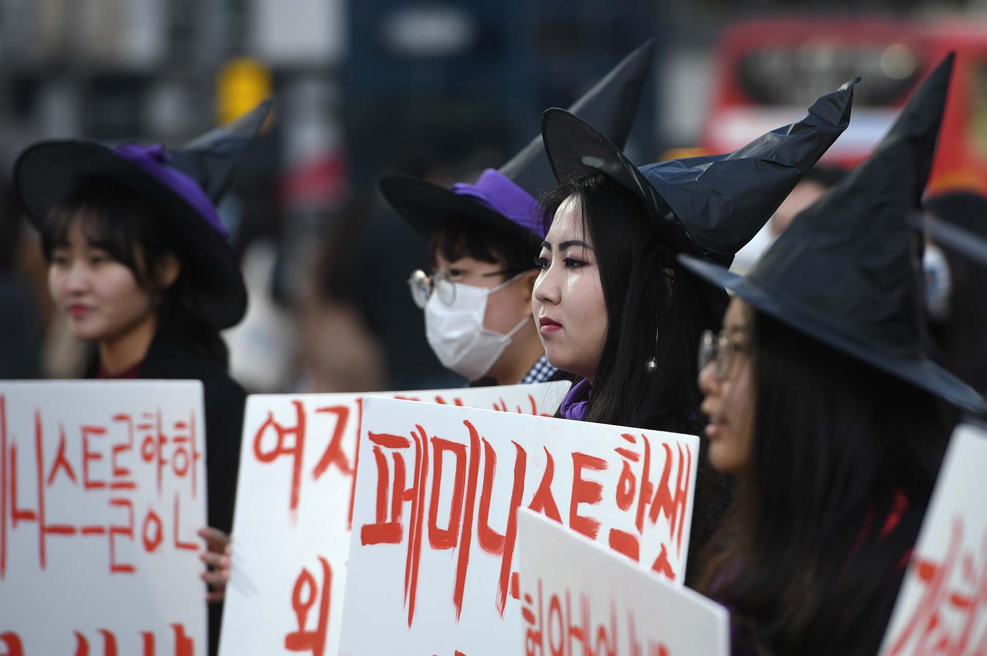 Mujeres surcoreanas vestidas de brujas sostienen pancartas feministas (Photo by JUNG Yeon-Je / AFP)