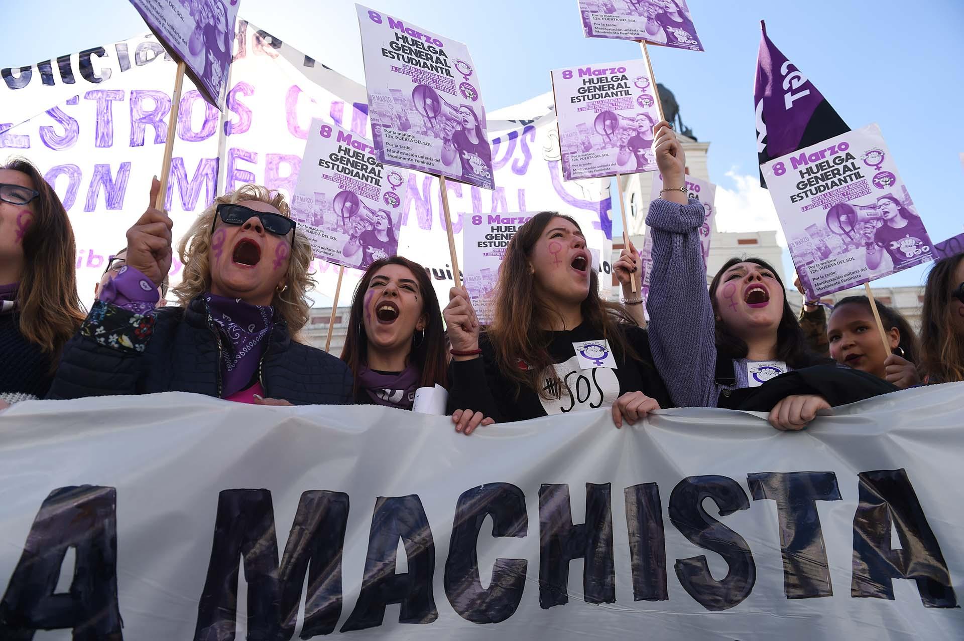 """Mujeres sostienen carteles con las consignas: """"Huelga general de estudiantes contra la violencia machista , el patriarcado y la justicia franquista, y la opresión capitalista"""", en Madrid (Photo by PIERRE-PHILIPPE MARCOU / AFP)"""