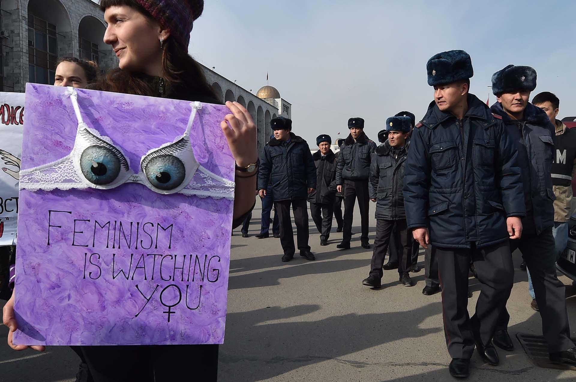 """Una mujer sostiene un cartel con la frase """"El feminismo te está observando""""en la protesta por el 8M en Bishkek, en Kirguistán (Photo by Vyacheslav OSELEDKO / AFP)"""