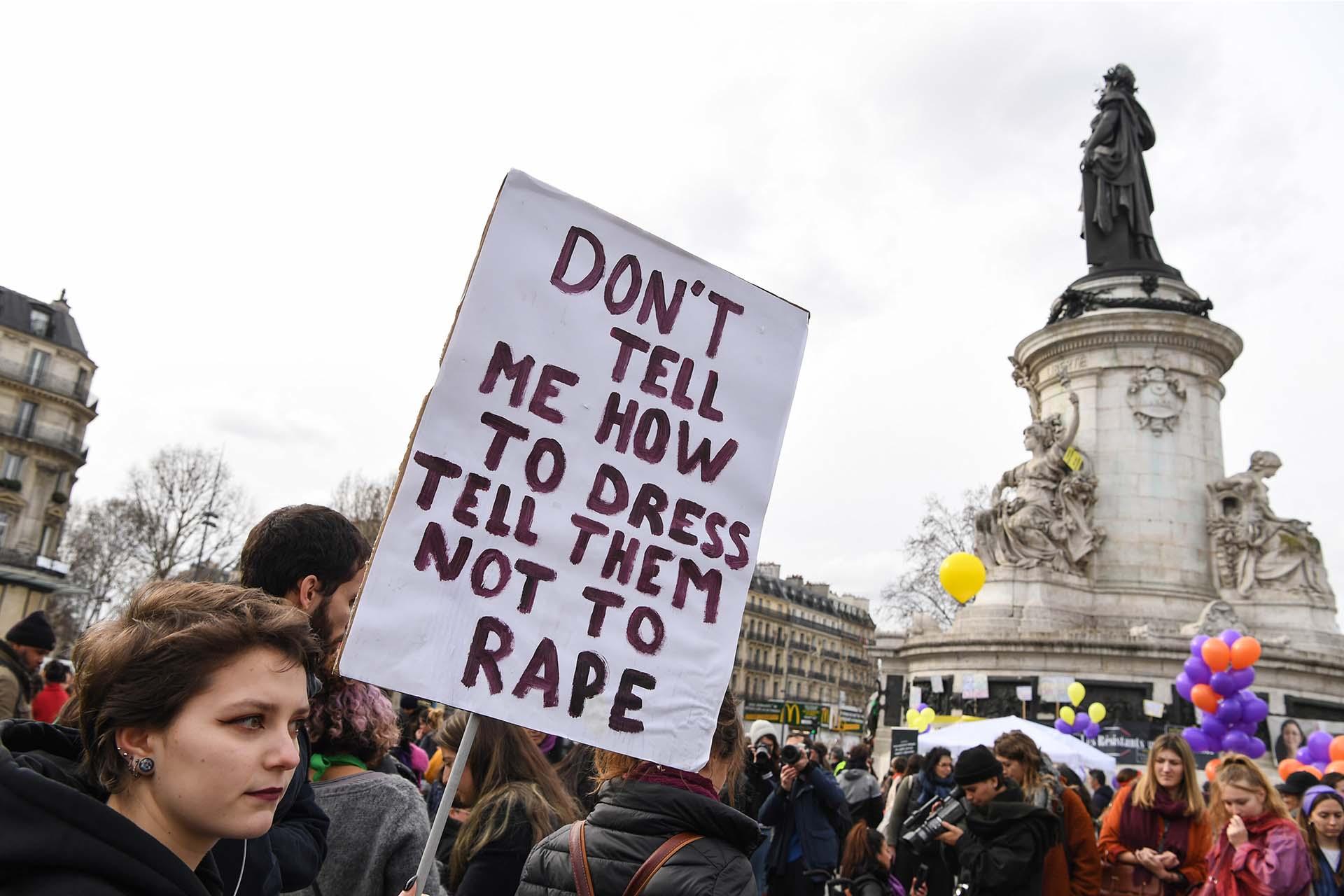 """Una joven sostiene una pancarta que dice """"No me digas cómo vestirme, diles a ellos que no me violen""""en Paris (Photo by Alain JOCARD / AFP)"""