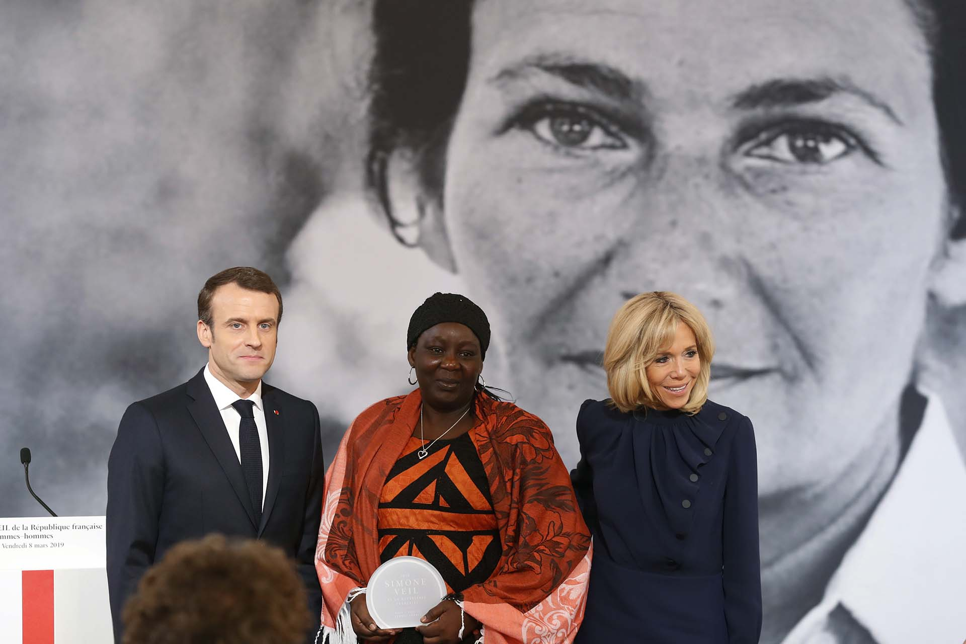 La activista camerunesa Aissa Doumara Ngatansou psoa junto al presidente francés Emmanuel Macron y su esposa, Brigitte Macron (Photo by Thibault Camus / POOL / AFP)