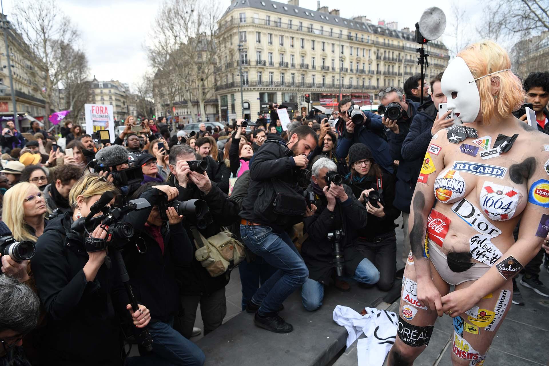 Una activista usa logos de marcas internacionales durante la protesta por el Día de la Mujer en París (Photo by Alain JOCARD / AFP)