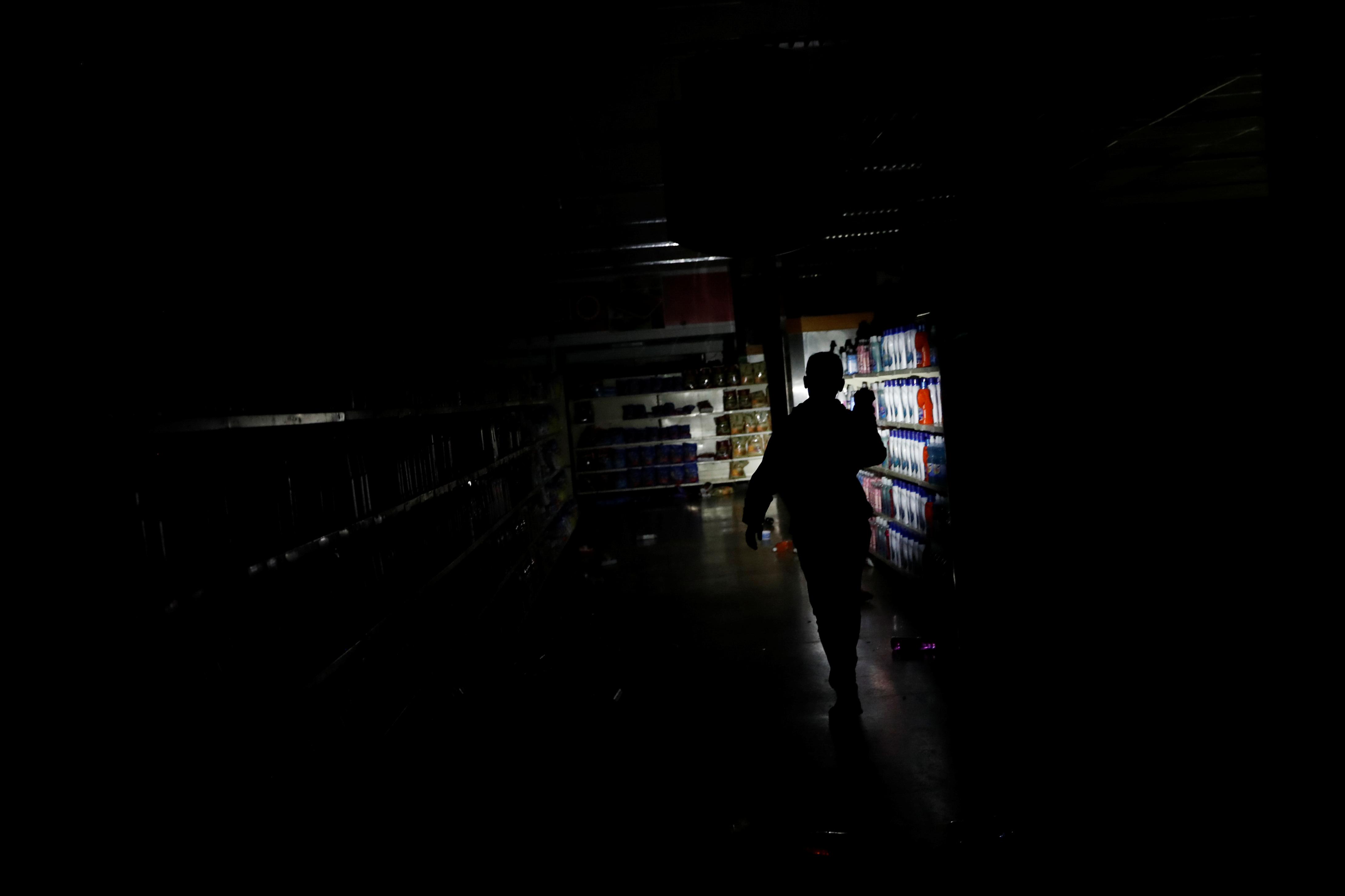 Un empleado inspecciona los daños en un supermercado de la capital