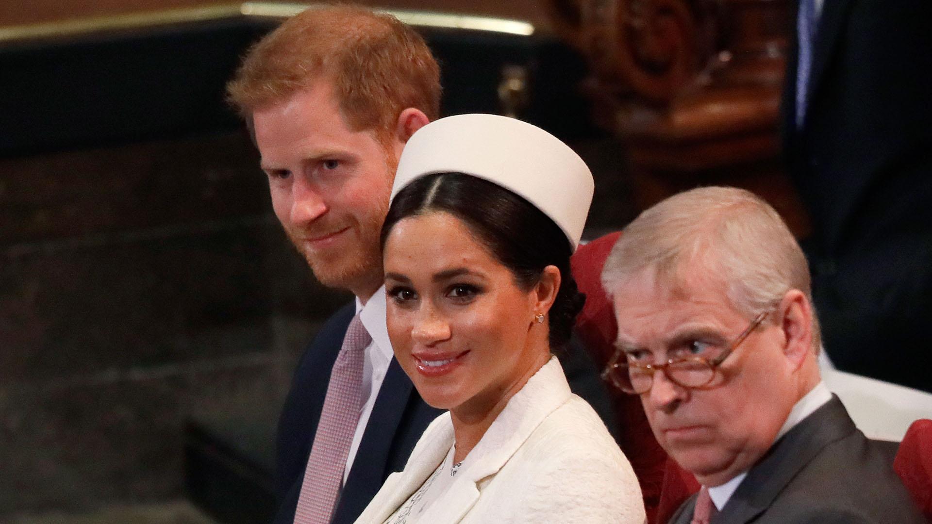 Más atrás el príncipe Harry junto a su esposa Meghan Markle