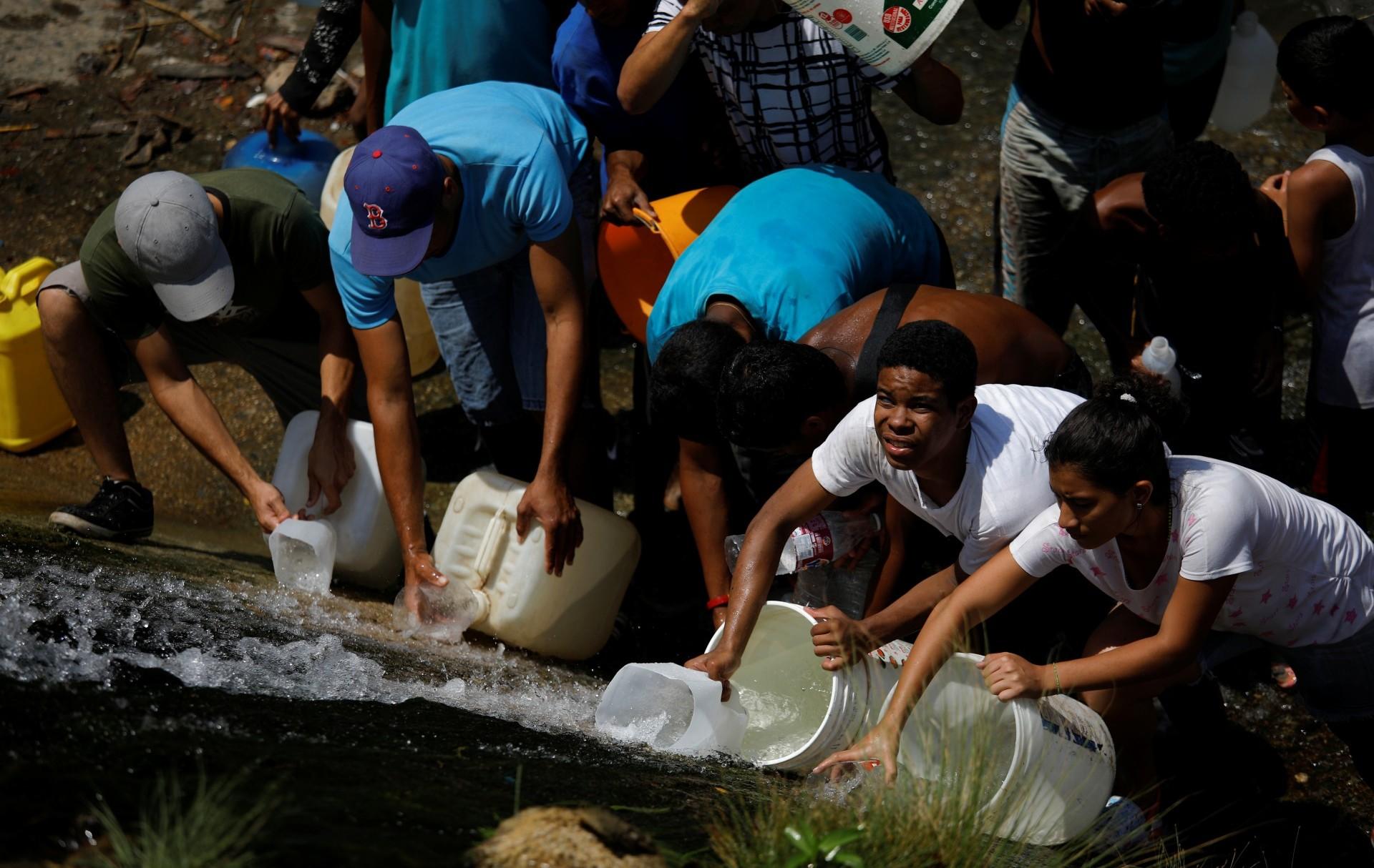 En una medida desesperada, un grupo de personas bajó este lunes al canal del infesto río Guaire, en Caracas, para surtirse del líquido en una bocatoma ubicada a un costado