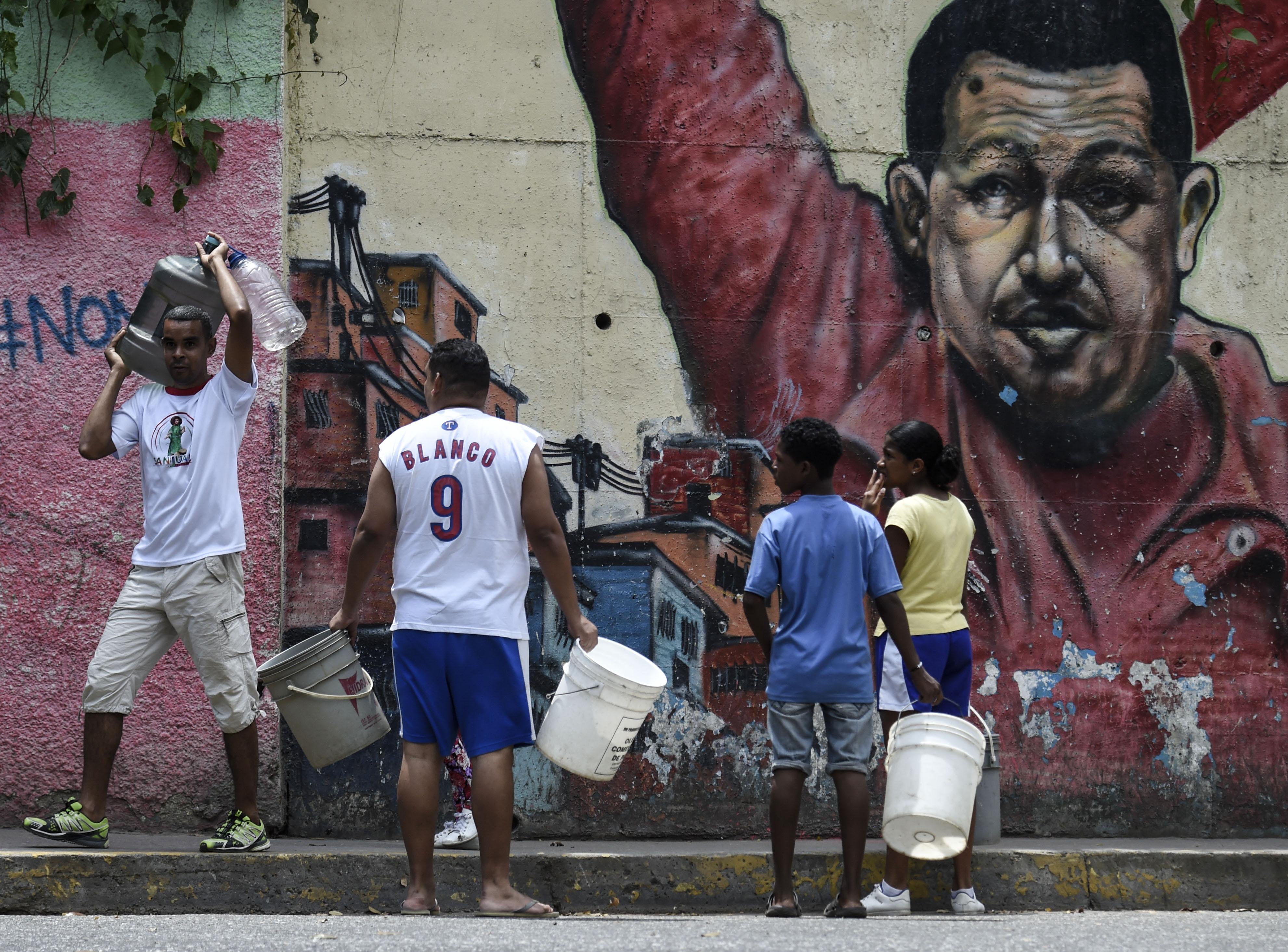 Una imagen del caudillo Hugo Chávez permanece pintada en la zona, mientras ciudadanos acuden con baldes para conseguir agua en las condiciones que sea