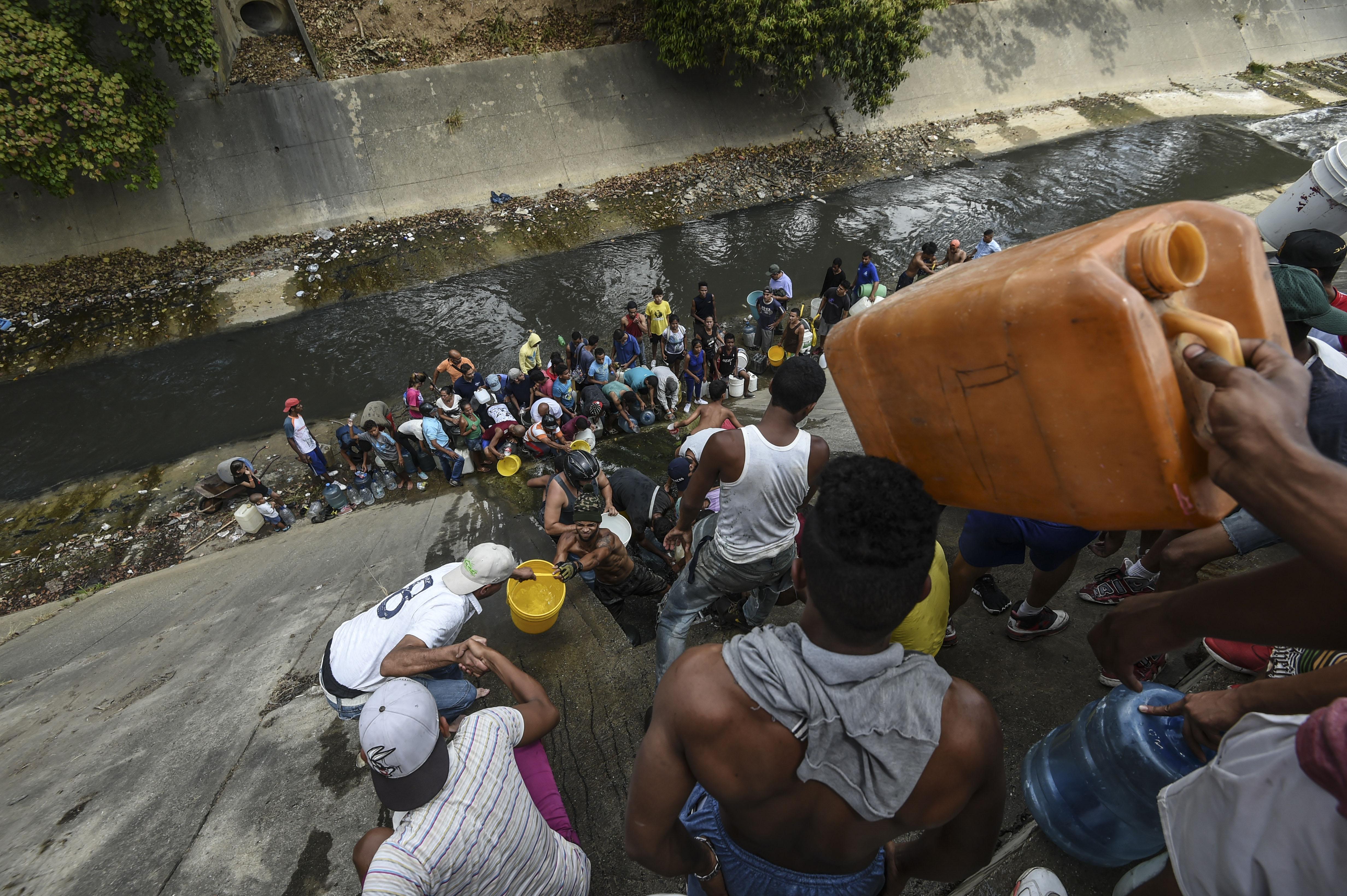 Decenas de personas buscan agua del río Guaire (Photo by JUAN BARRETO / AFP)