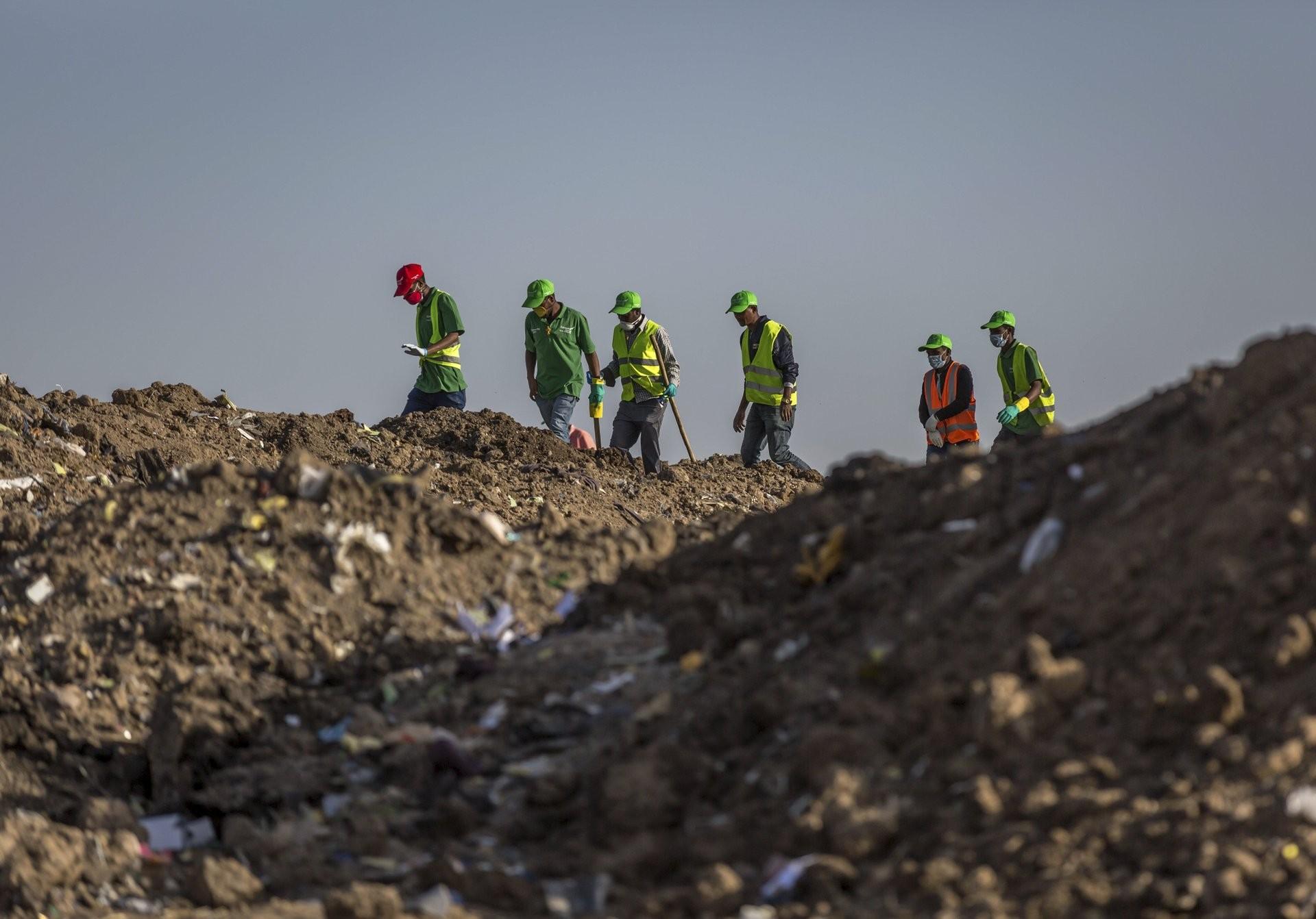 Trabajadores recolectan ropa y otros materiales, bajo la instrucción de los investigadores, en el lugar donde se desplomó el Boeing 737 Max 8 (Foto: AP)
