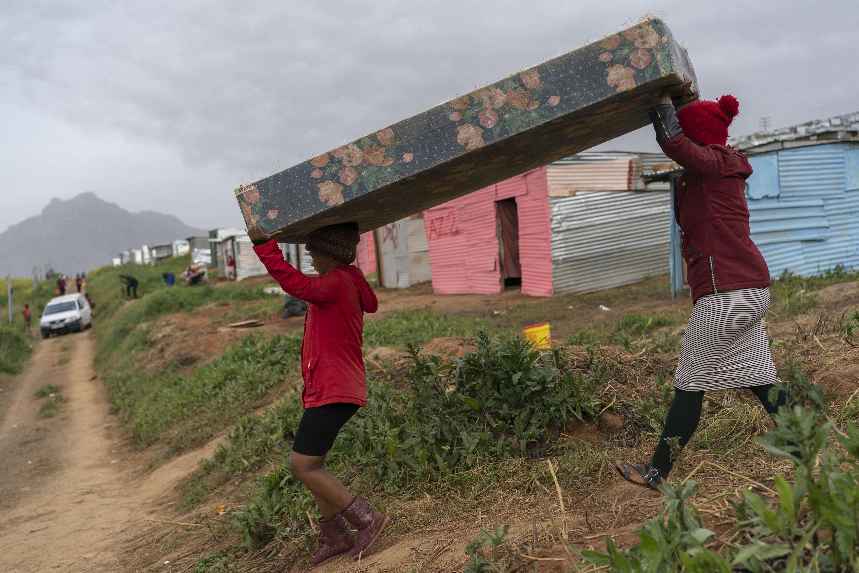 Cargando un colchón a una choza recién construida. (Joao Silva/The New York Times)