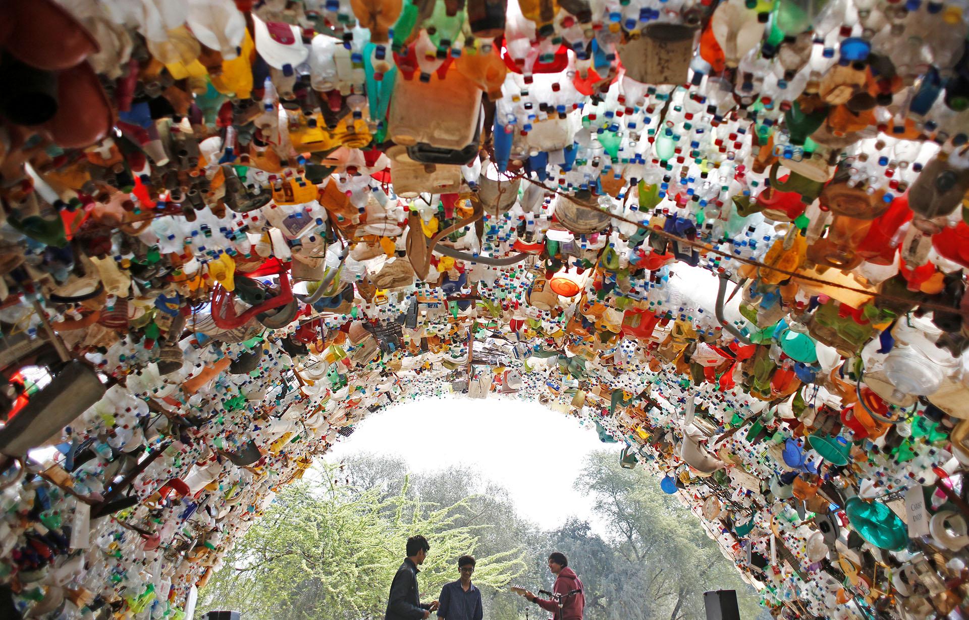 Jóvenes indios realizan una performance artística debajo de una estructura realizada con botellas plásticas como parte delas protestasglobales en la ciudad de Gurugram