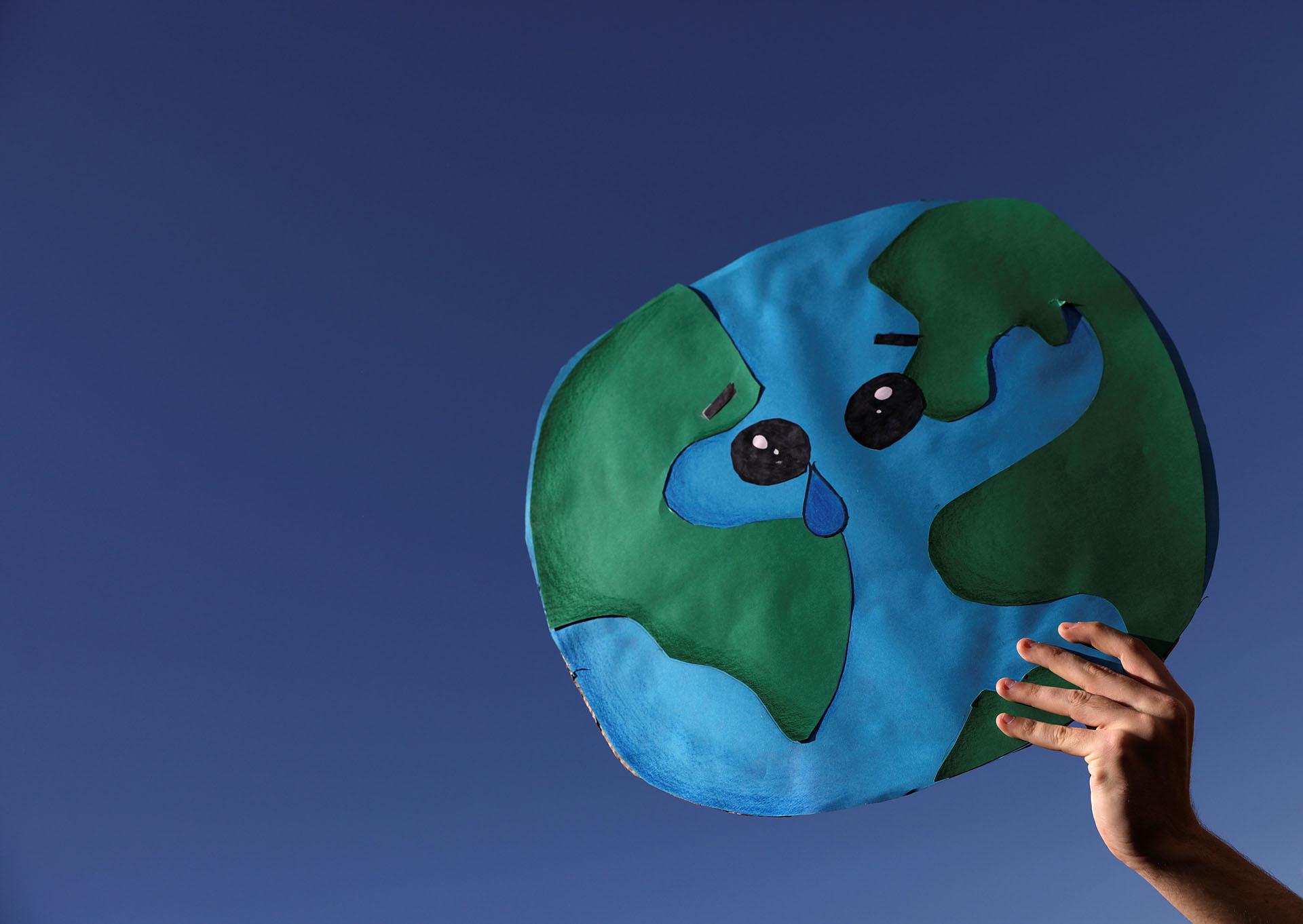 En Madrid,un estudiante sostiene un cartel con la Tierra llorando con un límpido cielo de fondo
