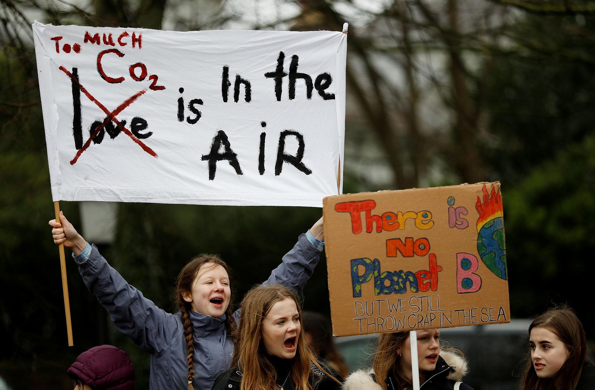 """Un cartel en Brighton asegura que """"Hay demasiado dióxido de carbono en el aire"""", en un juego de palabras con la canción """"El amor está en el aire"""" (""""Love is in the air"""")"""