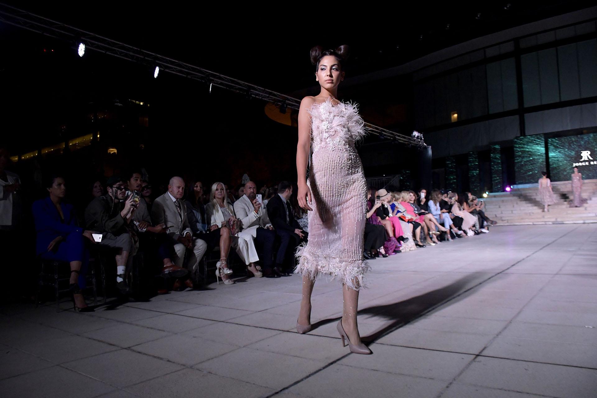 Al cuerpo, strapless, con plumas y perlas.Uno de los últimos diseños de la pasarelaJorge rey en tonalidades rosados
