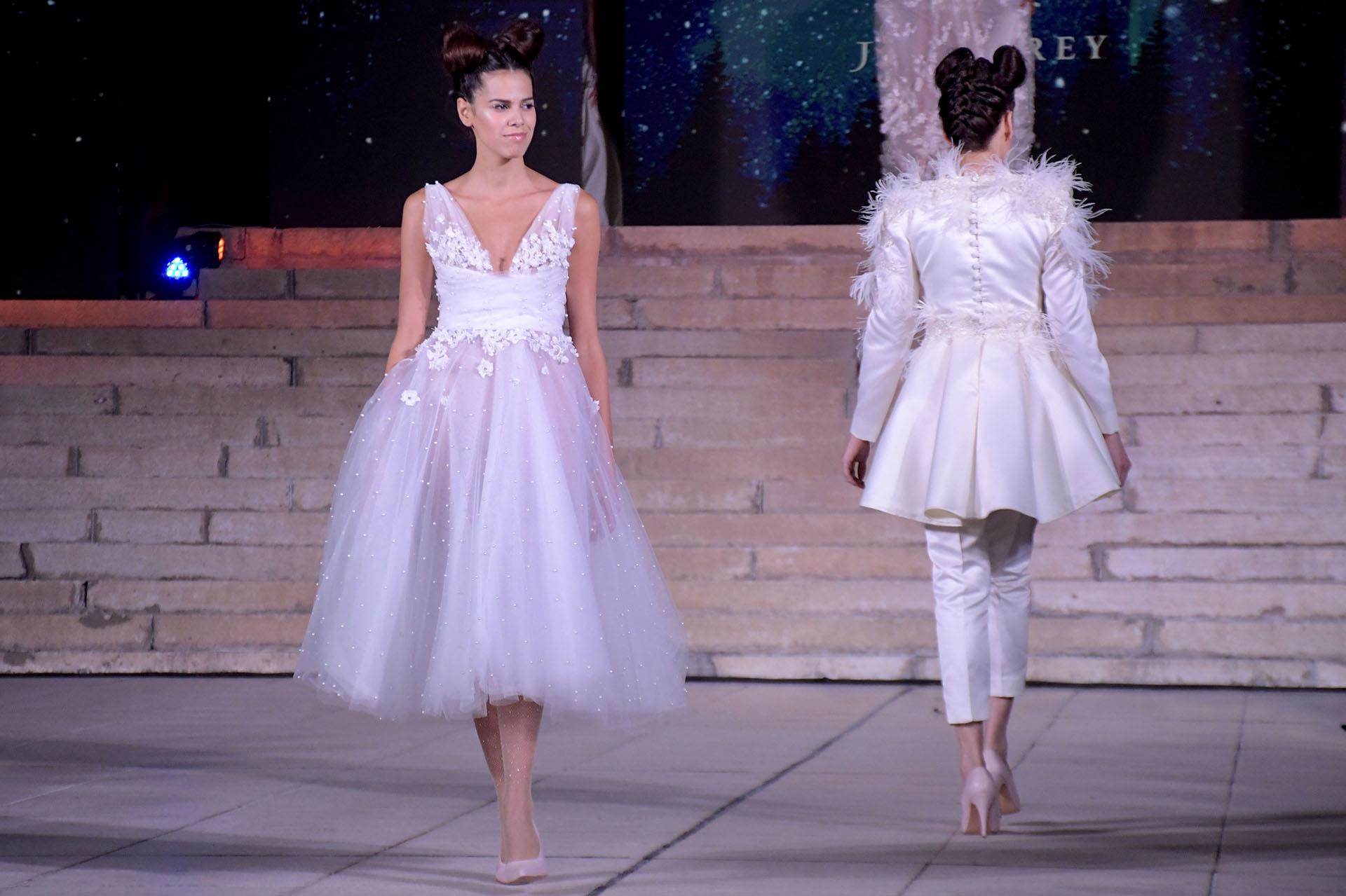 Un diseño corto con drapeado de tul en la cintura y con destellos de brillantes en la falda. El detalle romántico, las flores bordadas