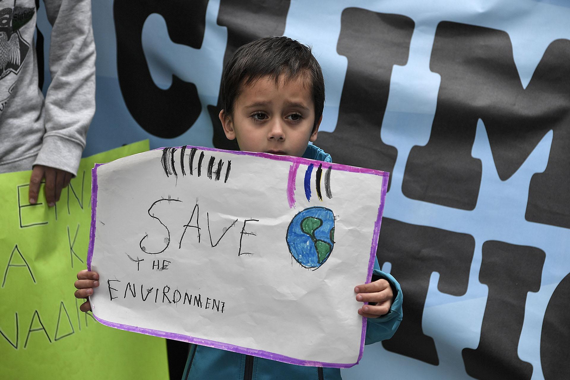 Un niño sostiene un cartel mientras participa en una manifestación contra el cambio climático en Atenas, en un día mundial de protestas estudiantiles con el objetivo de impulsar a los líderes mundiales a la acción contra el cambio climático, el 15 de marzo de 2019. - Las protestas mundiales fueron inspiradas por un adolescente sueco la activista Greta Thunberg, quien acampó frente al parlamento en Estocolmo el año pasado para exigir la acción de los líderes mundiales contra el calentamiento global. (Foto de Louisa GOULIAMAKI / AFP)