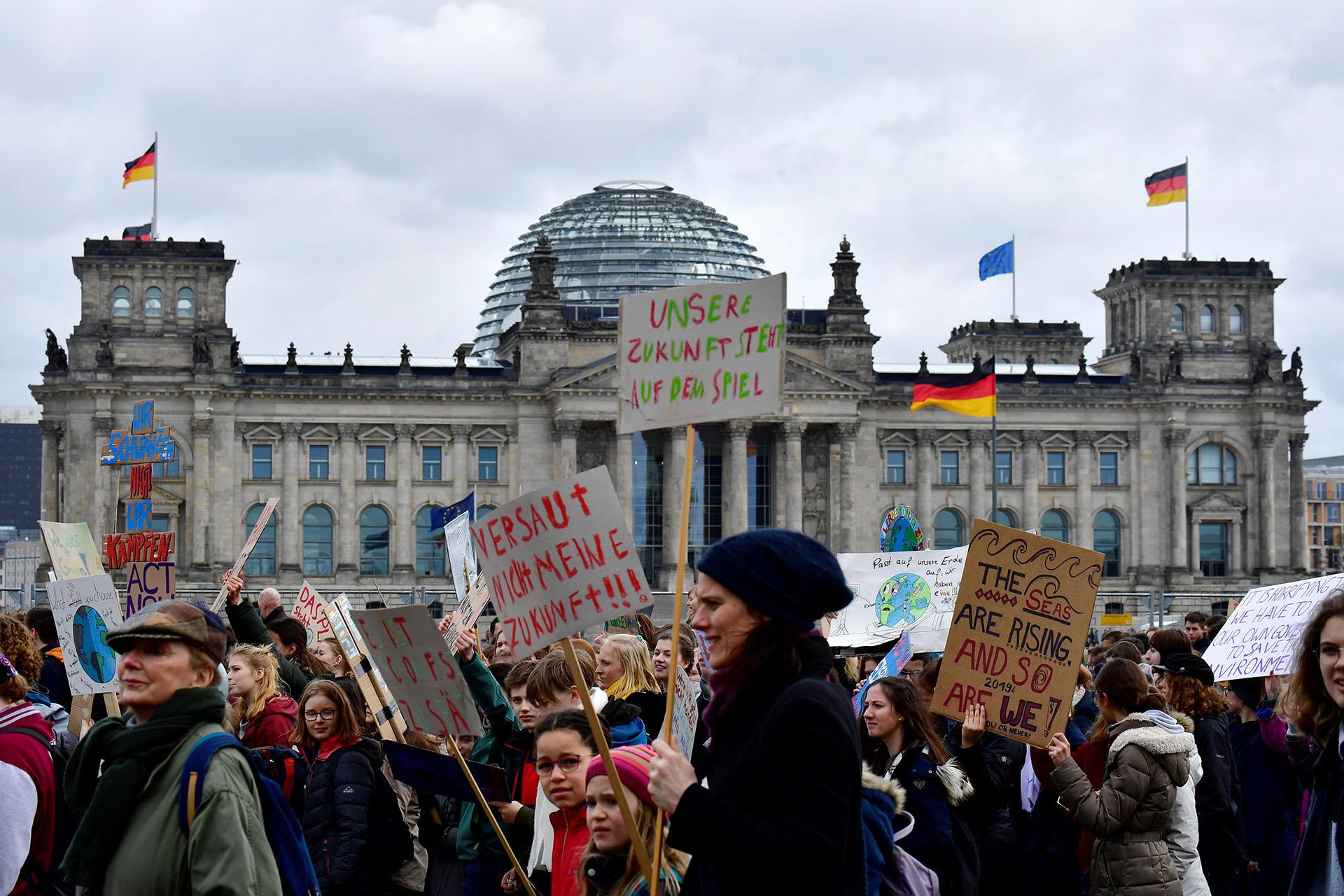 """Los jóvenes pasan por el edificio del Reichstag que alberga al parlamento alemán (Bundestag) durante el movimiento """"Viernes para el Futuro"""" en un día mundial de protestas estudiantiles con el objetivo de incitar a los líderes mundiales a actuar sobre el cambio climático el 15 de marzo de 2019 en Berlín. - Las protestas en todo el mundo fueron inspiradas por la activista sueca Greta Thunberg, quien acampó frente al parlamento en Estocolmo el año pasado para exigir la acción de los líderes mundiales sobre el calentamiento global. (Foto por Tobias SCHWARZ / AFP)"""