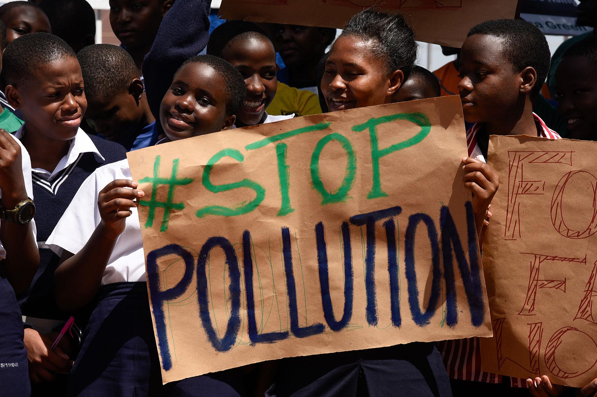 Los estudiantes sostienen pancartas durante una huelga como parte de un día mundial de protestas estudiantiles con el objetivo de incitar a los líderes mundiales a la acción sobre el cambio climático en la escuela cristiana joven de Najjanankumbi en Kampala, Uganda, el 15 de marzo de 2019. - Las protestas mundiales fueron inspiradas por un sueco activista adolescente, quien acampó frente al parlamento en Estocolmo el año pasado para exigir la acción de los líderes mundiales contra el calentamiento global. (Foto por Isaac Kasamani / AFP)