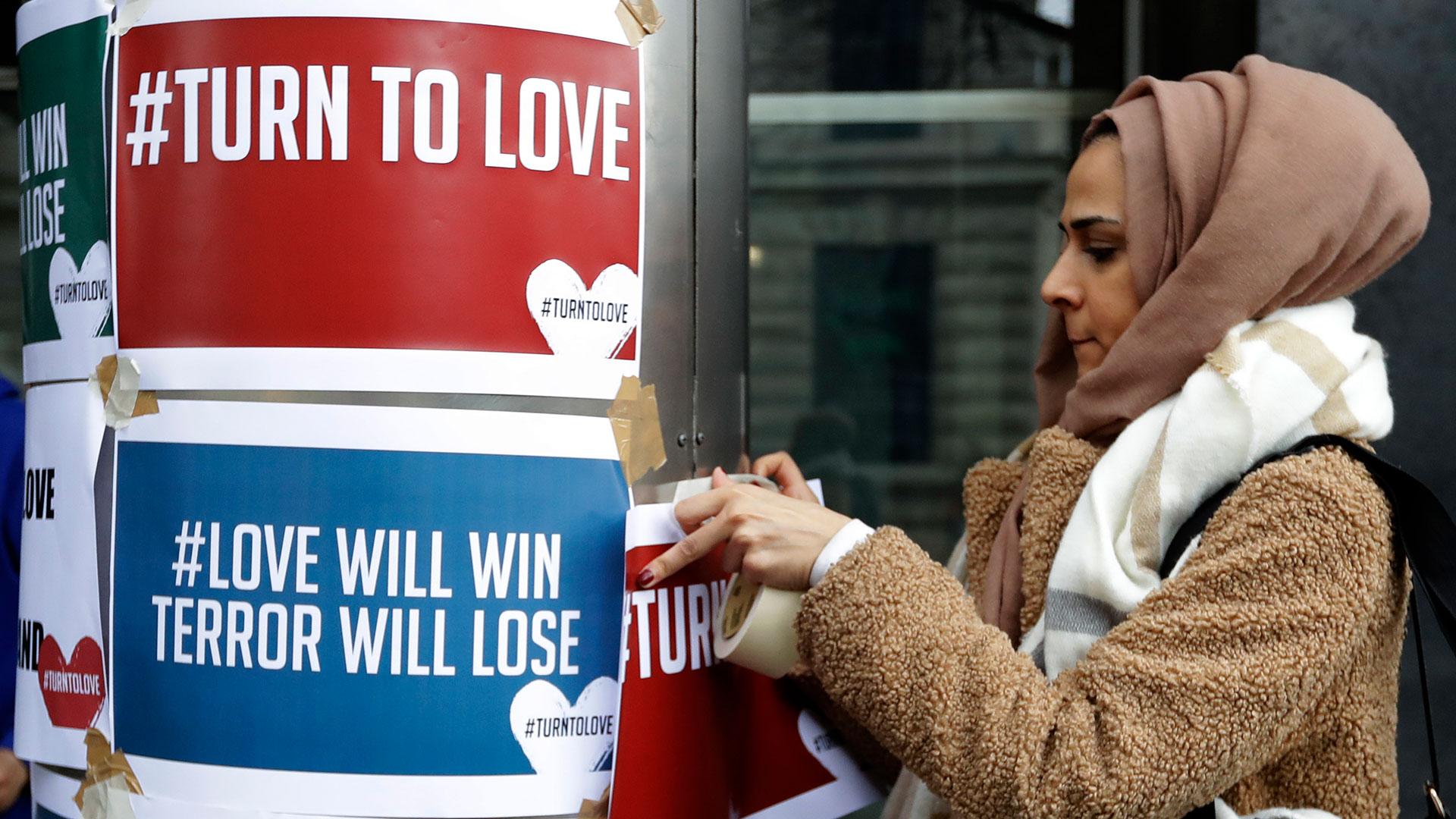 Un manifestante cuelga pancartas del grupoecuménico 'Turn to Love' (Volver al amor) en una vigilia en la Casa de Nueva Zelanda en Londres (Foto: AP)