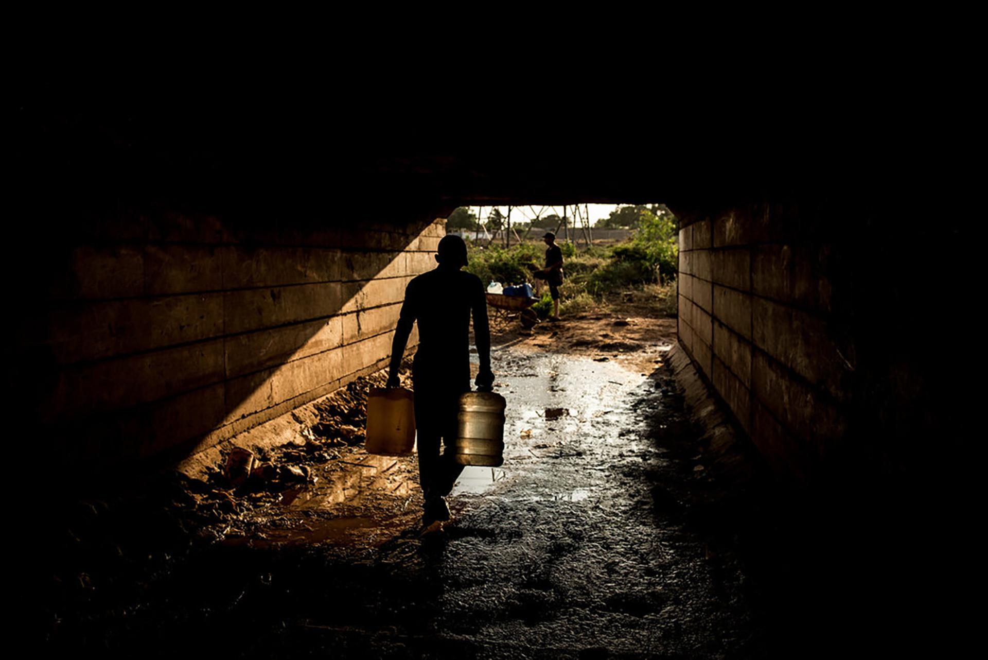 La falta de energía acaba pronto con el agua potable y las personas recogen líquido de donde pueden. Aquí,debajo de un puente en Maracaibo. (Meridith Kohut para The New York Times)