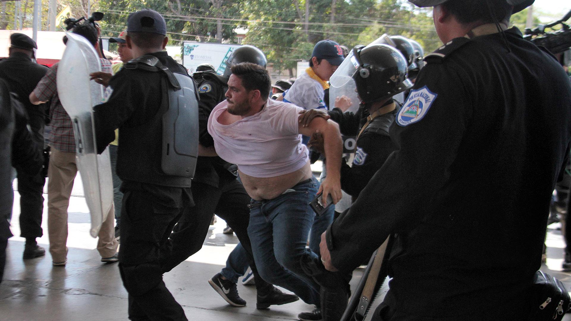 Un agente de la policía de Nicaragua forcejea con el fotógrafo de AFP Luis Sequeira en medio de las detenciones de dirigentes opositores este sábado en Managua (Photo by Maynor Valenzuela / AFP)