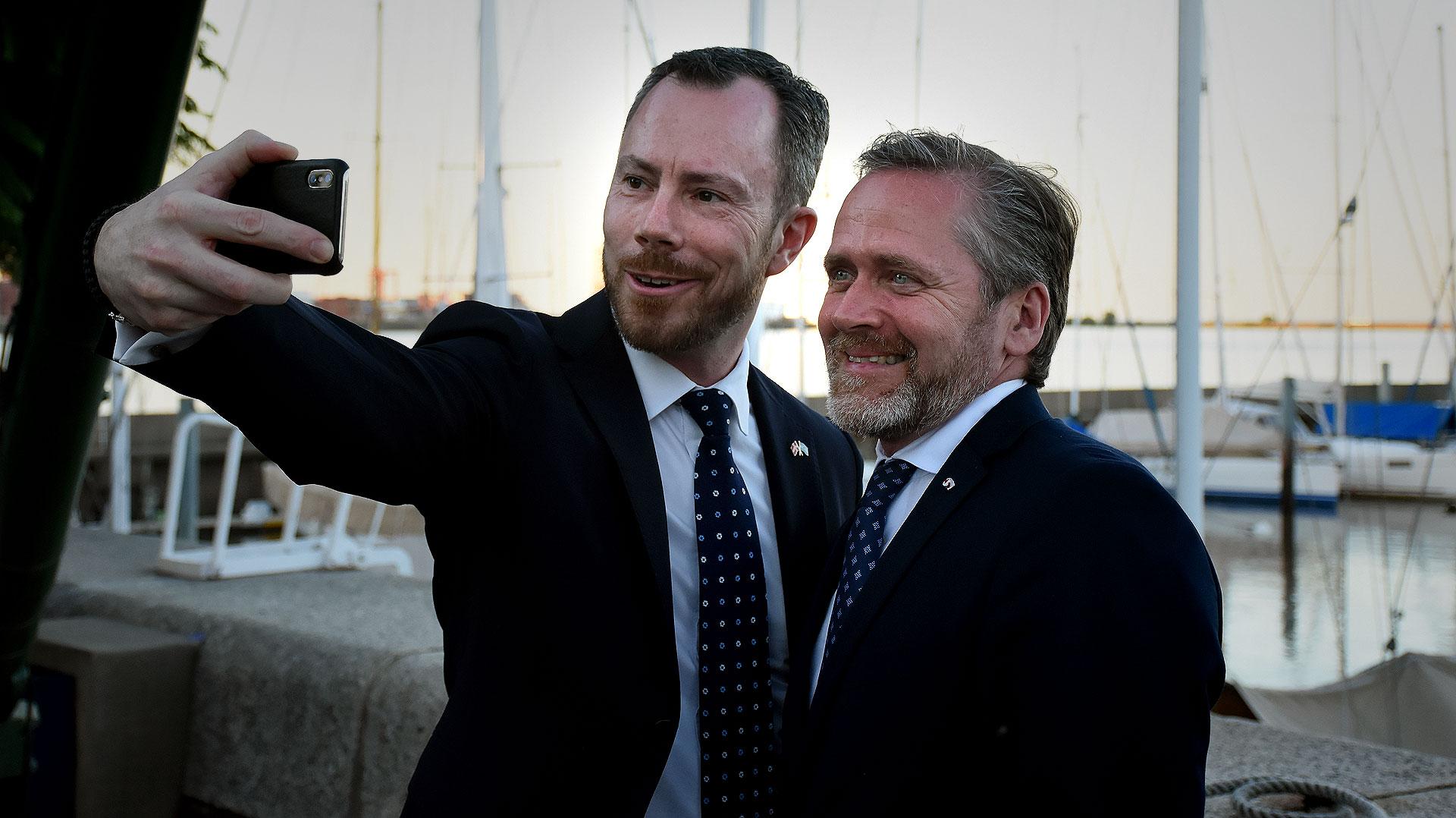 El ministro de Medio Ambiente y Agricultura, Jakob Ellemann-Jensen y Ministro de Relaciones Exteriores, Anders Samuelsen, posan juntos para un selfie con la imagen del atardecer en Puerto Madero