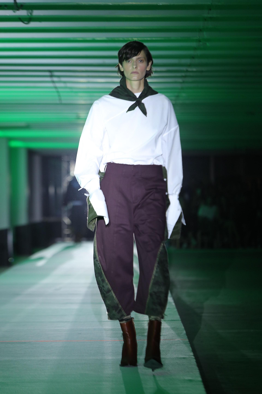Un tradicional buzo de JT blanco con mangas XL combinado con tela impermeable verde. Para completar el look, pantacourt bicolor violeta y verde impermeable. Como accesorio, un pañuelo en su cuello
