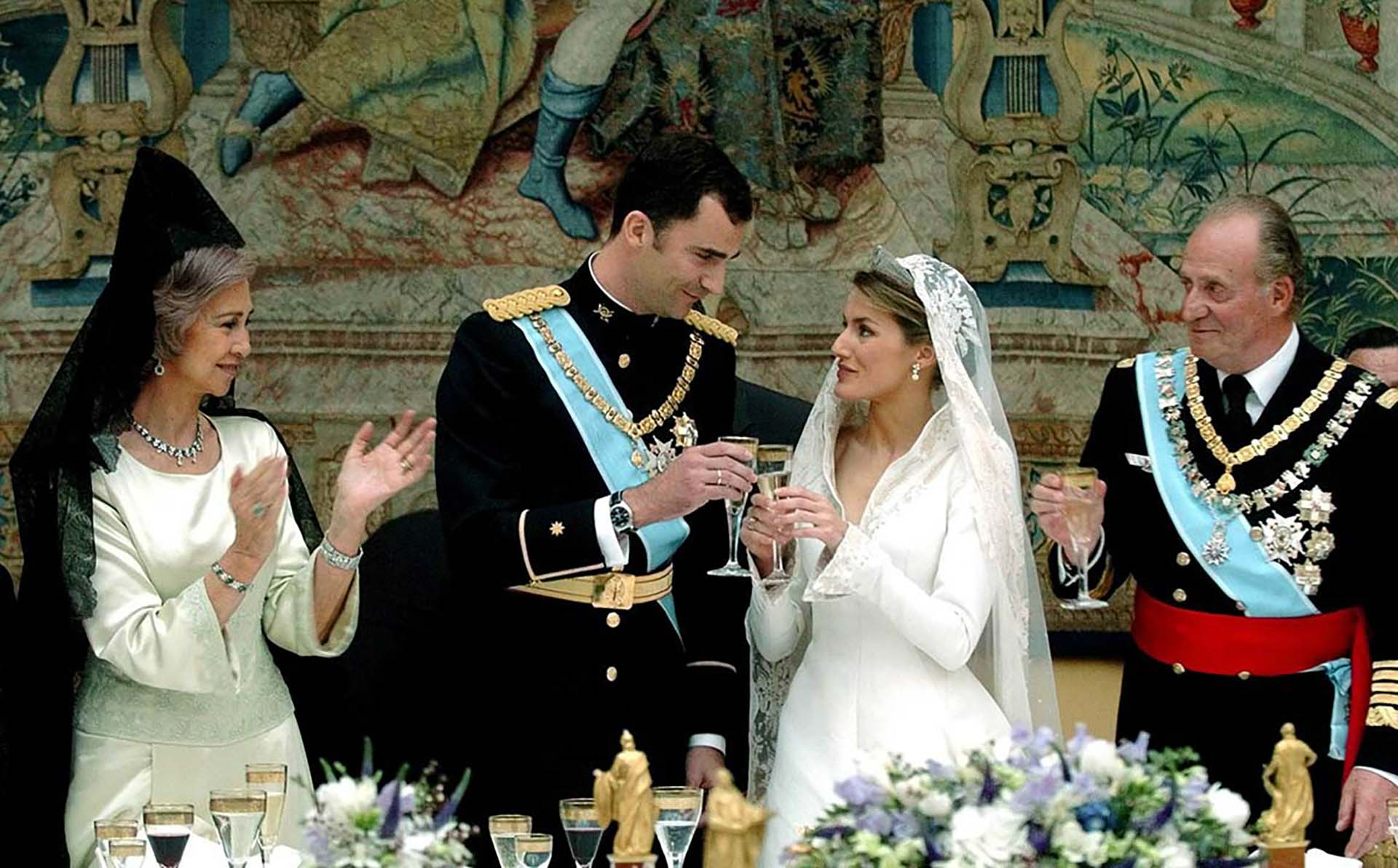 Spanish Crown Prince Felipe (2nd L) and his bride Letizia Ortiz, Princess of Asturias, (CR) toast as King Juan Carlos (R) and Queen Sofia look on at the start of their wedding banquet at Madrid's Royal Palace May 22, 2004. [Prince Felipe married former television presenter Ortiz in a glittering ceremony symbolising a new dawn for Spain two months after the deadly Madrid train bombings.]