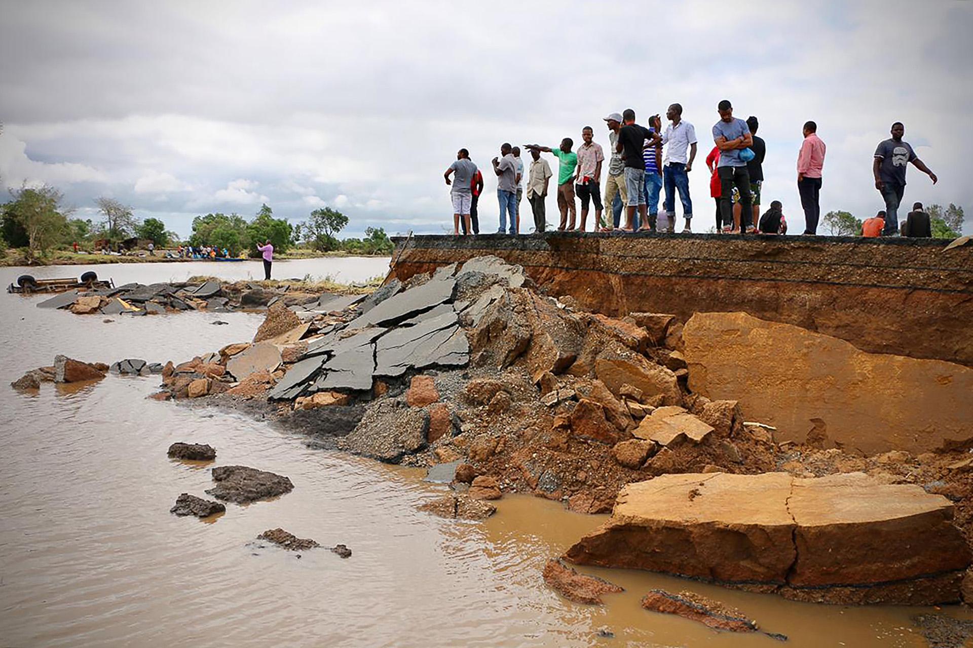 Los locales se ubican junto a una sección dañada de la carretera entre Beira y Chimoio en el distrito de Nhamatanda, en el centro de Mozambique, el 19 de marzo (Photo by ADRIEN BARBIER / AFP)