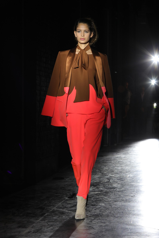 Los géneros de crêpe, el favorito de Evangelina Bomparola para cada temporada. En pasarela, una blusacon lazo en el cuello bicolor en color marrón habano con coral, pantalón recto y blazer a tono de la blusa.