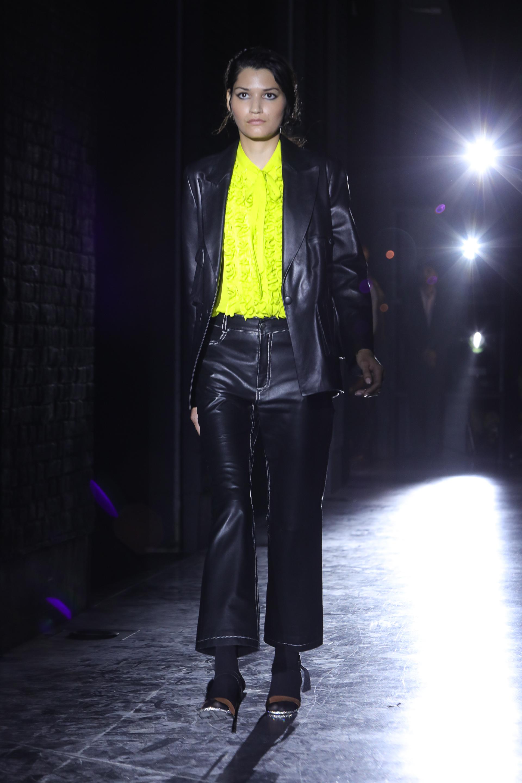 Los conjuntos de pantalón y saco de la nueva colección son de cuero de oveja elastizado. En pasarela, el look combinado es en color negro con detalles de hilo blanco. La blusa con jabot en verde lima.