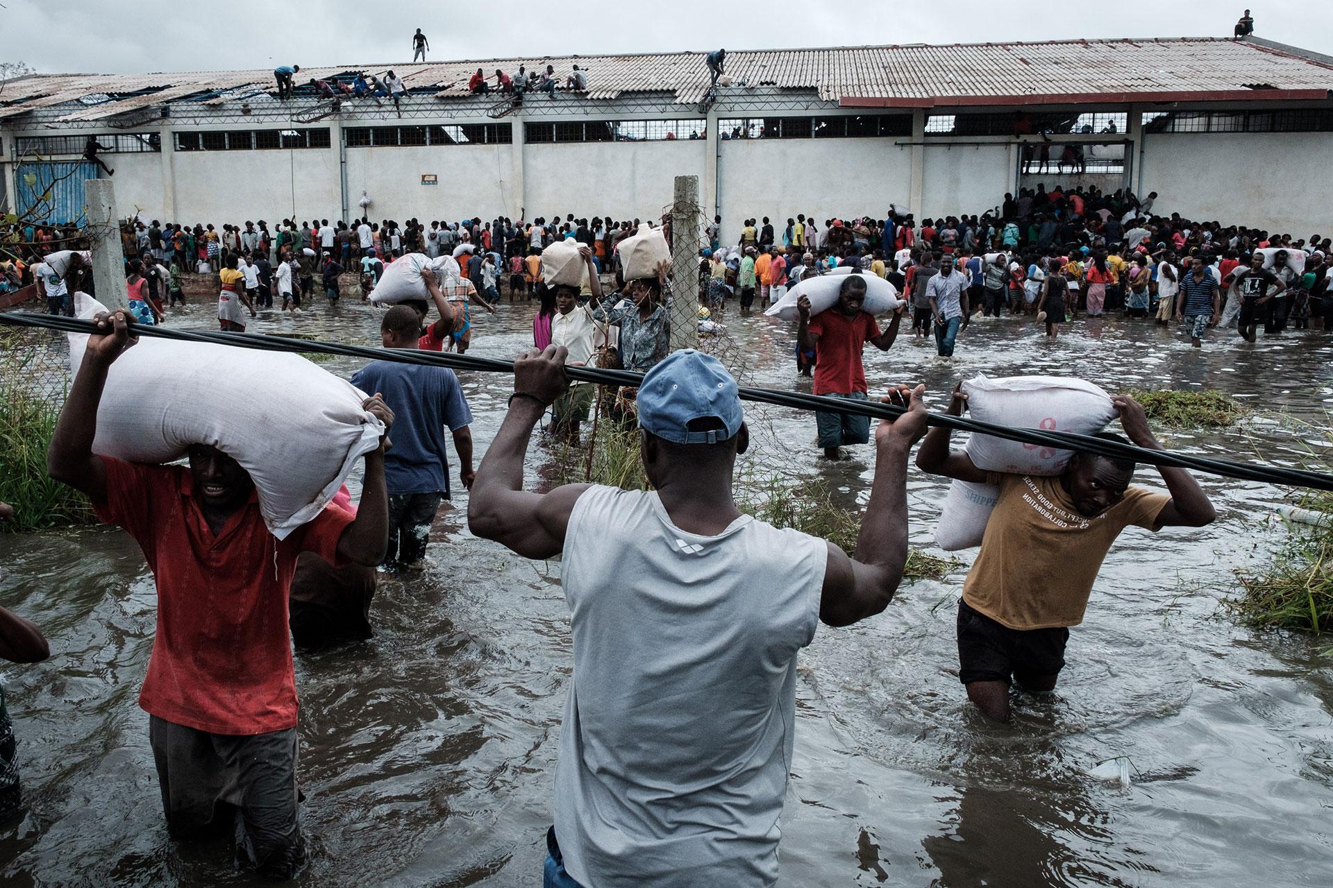 Un grupo de hombres traslada bolsas de arroz que llegó como parte de la ayuda humanitaria (Foto: Yasuyoshi CHIBA / AFP)