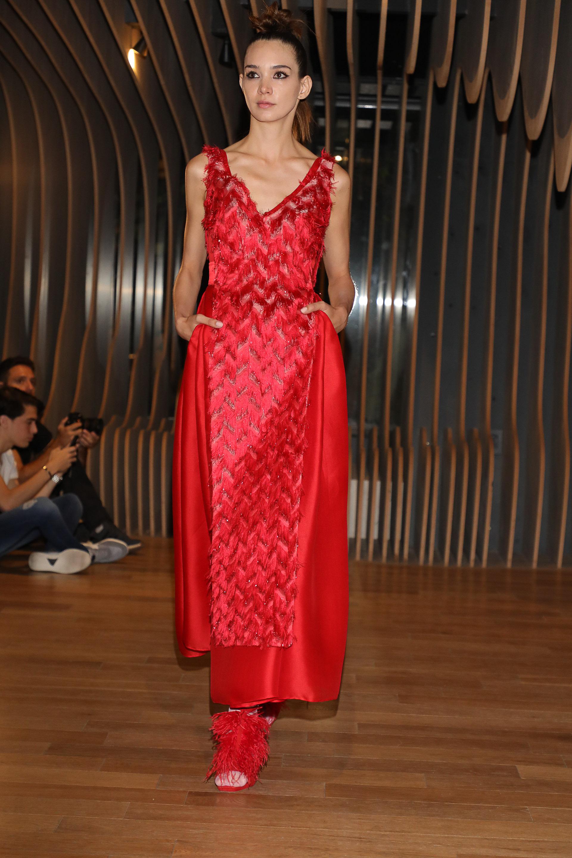 El color rojo es un clásico en las colecciones del modisto. Un comodín. Con bolsillos y al tobillo. Sin mangas y escote V. El detalle chic, el bordado de plumas