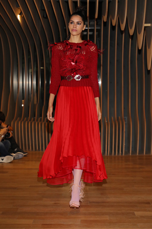 Plisado. Falda color rojo de la colección Oniria de gasa que completó el look de la blusa con detalles de flores y plumas