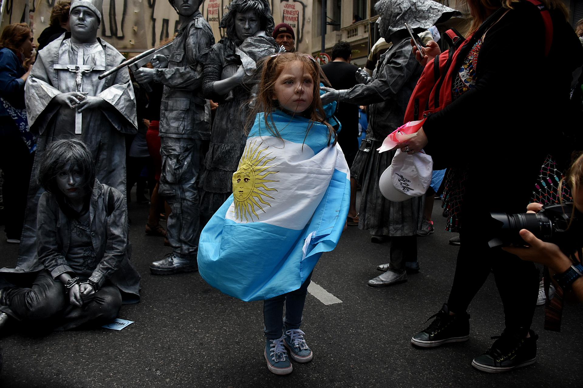 Una nena con la bandera argentina en medio de la marea de gente
