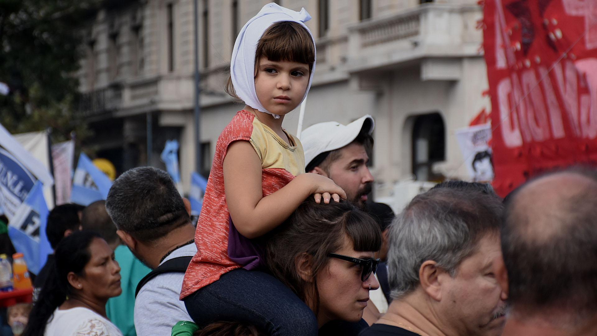 Una nena de 4 años que atrapó todas las miradas, con un pañuelo de las Madres en la cabeza desde los hombros de su mamá