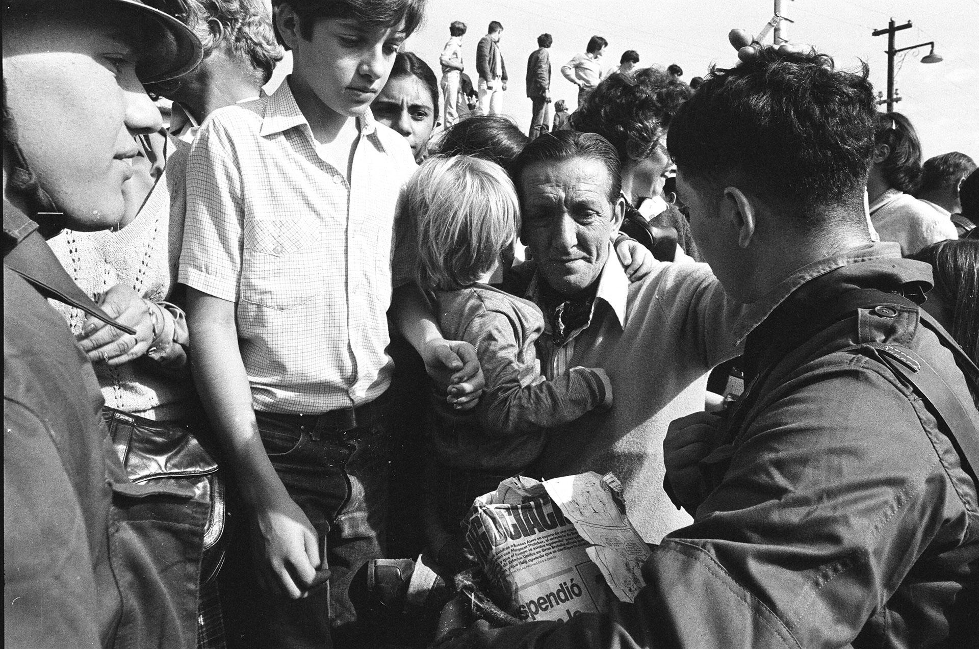 El padre abraza a su hijo pequeño y despide al mayor que parte hacia las islas Malvinas. Hay una emoción contenida e incertidumbre por lo que pueda ocurrir. (Foto: Juan Sandoval)