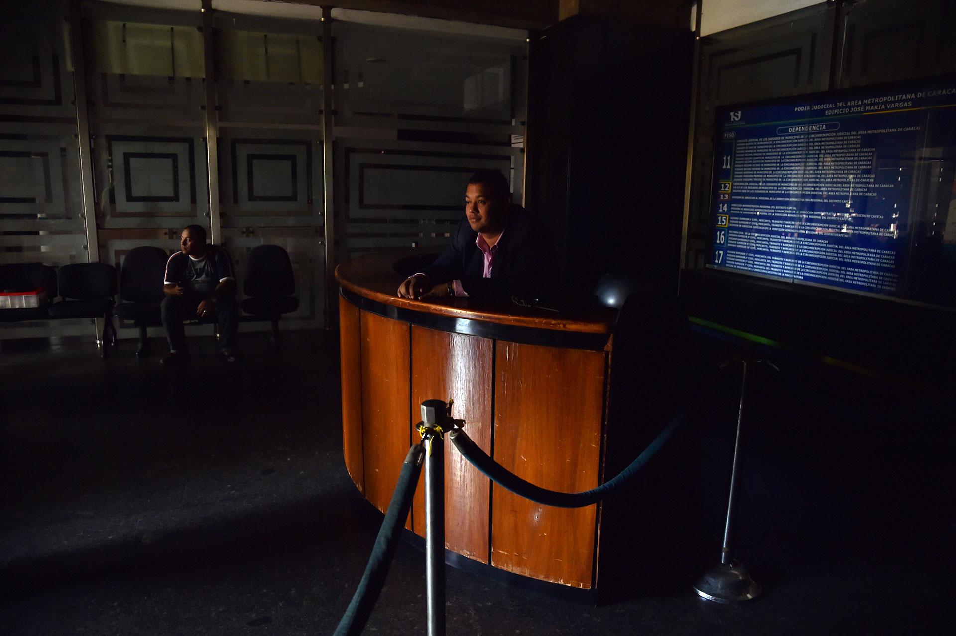 Un hombre sentado en la recepción de una oficina dentro del edificio de la Asamblea Nacional (AFP)