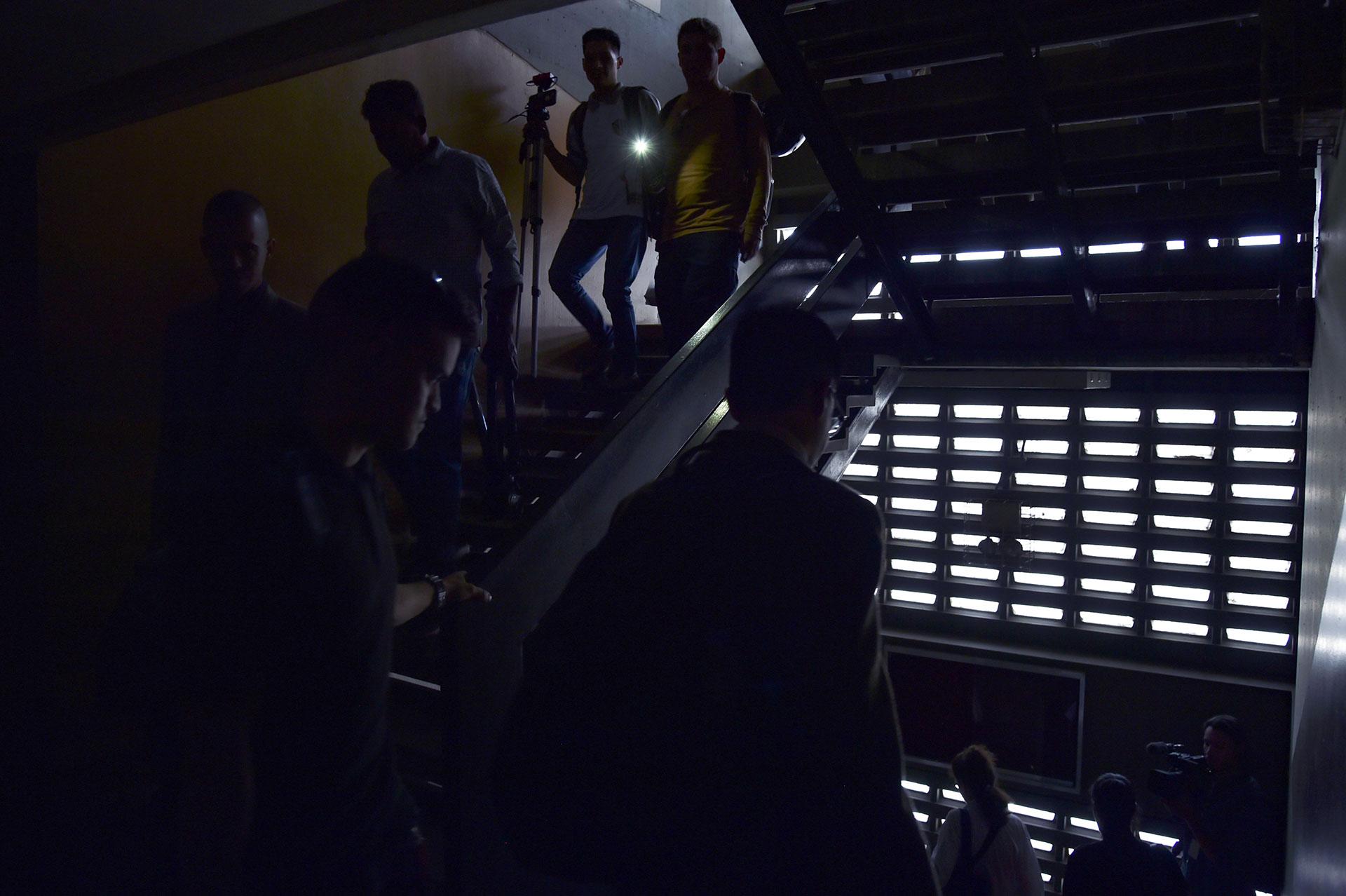 La gente evacua el edificio de la Asamblea Nacional de Venezuela durante un apagón parcial en Caracas el 25 de marzo de 2019. (AFP)