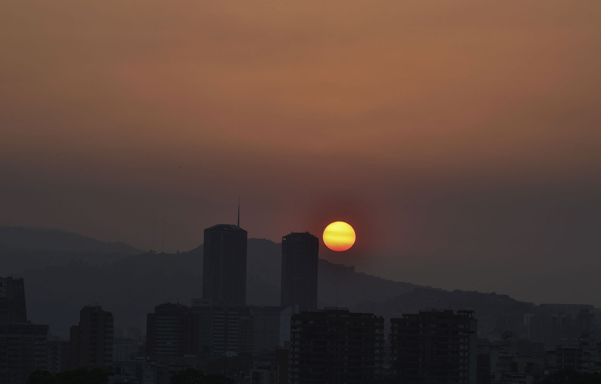 El sol se pone sobre una Caracas a oscuras durante el corte de luz que comenzó el 25 de marzo de 2019. (AFP)
