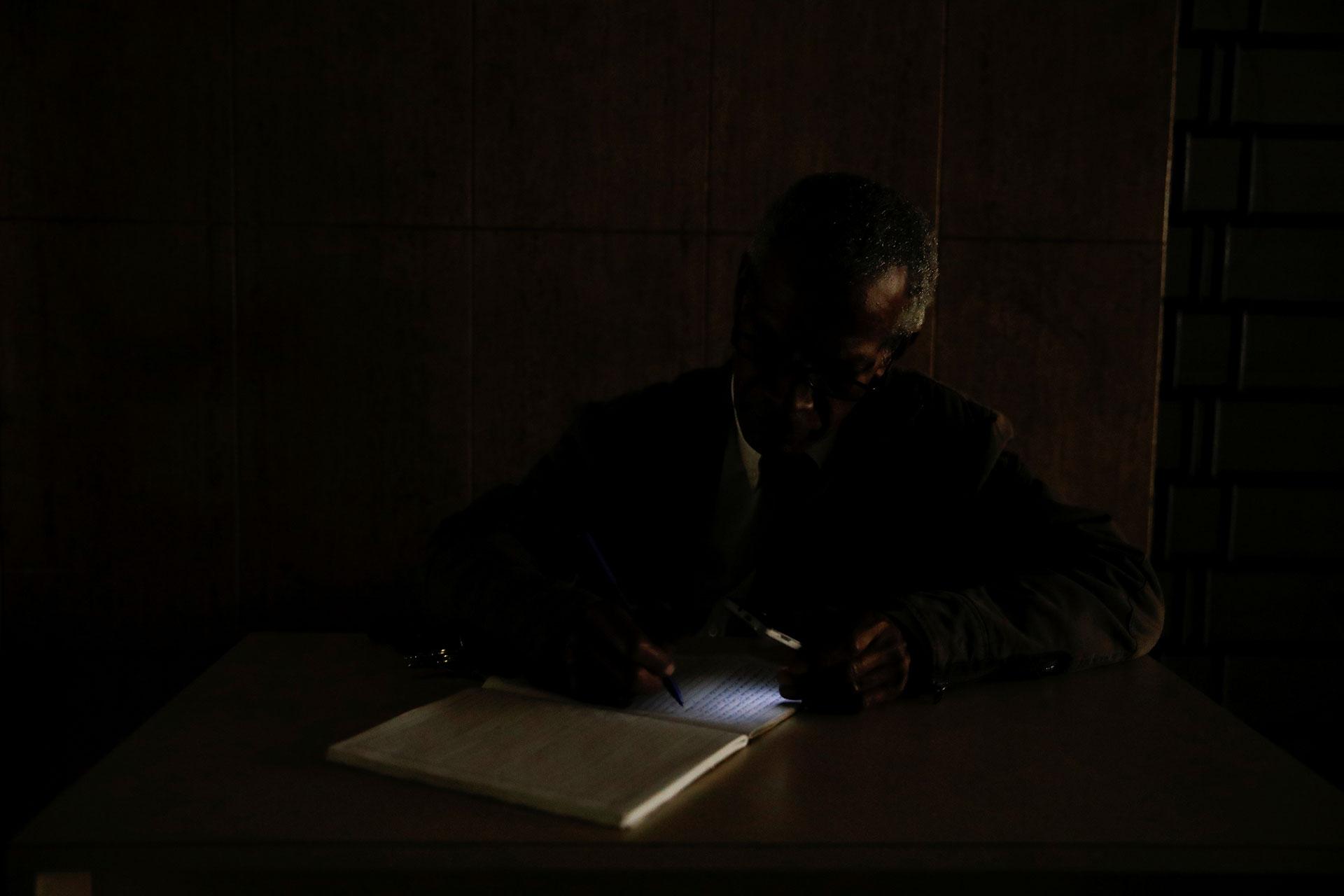 Un guardia de seguridad usa la linterna de su celular para iluminar un libro duranteel apagón masivo en Venezuela (Reuters)