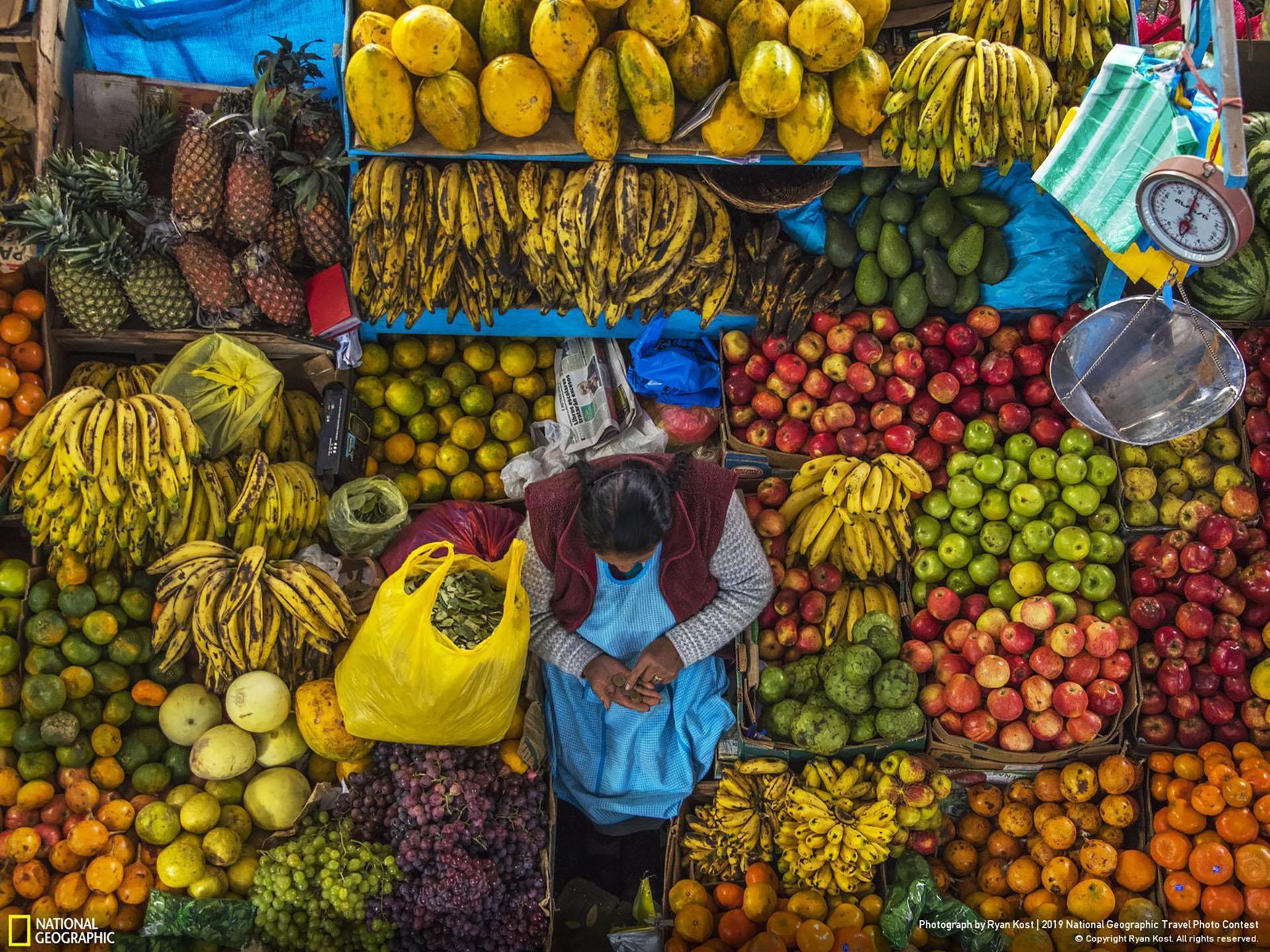"""""""Día del Mercado"""", por Ryan Kost: """"Día de mercado en Urubamba. Hermosa, deliciosa, orgánica, y muy colorida. Siempre es más saludable aquí. Las únicas cosas que están siendo procesadas son tus pensamientos haciendo cosquillas a tus sentidos. Mi rutina diaria. Parar aquí por la mañana. Mezclar esta bondad en un batido fresco y guardar un poco para una copa a las cinco de la tarde con pisco. Mi consejo…. si quieres experimentar más sobre una cultura, visita el mercado local"""". (""""Market Day"""" / 2019 National Geographic Travel Photo Contest / Categoría: Gente / Ubicación: Urubamba, Cuzco, Perú)"""