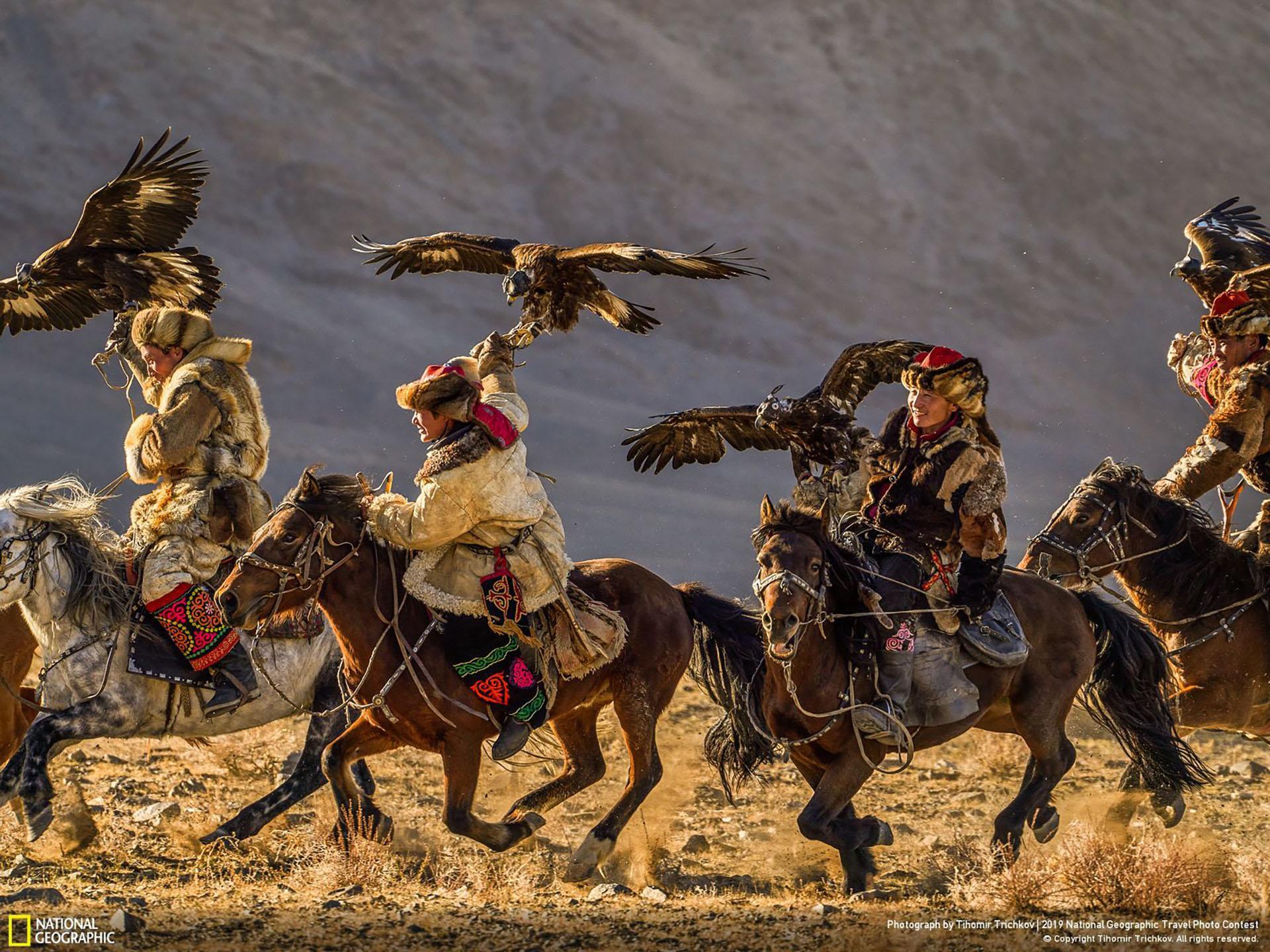 """""""Cabalgamos juntos, volamos juntos"""", por Tihomir Trichkov: Los participantes del Festival de la Águila Dorada (Golden Eagle Festival) -un festival anual tradicional celebrado en el aymag de Bayan-Ölgiy, una de las 21 provincias en la parte más occidental de Mongolia- muestran sus habilidades. Los cazadores de águilas celebran su herencia kazaja y compiten para capturar pequeños animales, como conejos y zorros. La caza del águila se ha practicado en Asia Central desde hace miles de años, aunque hoy en día solo se conserva en la cultura kazaja, donde las tradiciones siguen vivas y bien conservadas. (""""We Ride Together, We Fly Together"""" / 2019 National Geographic Travel Photo Contest / Categoría: Personas)"""