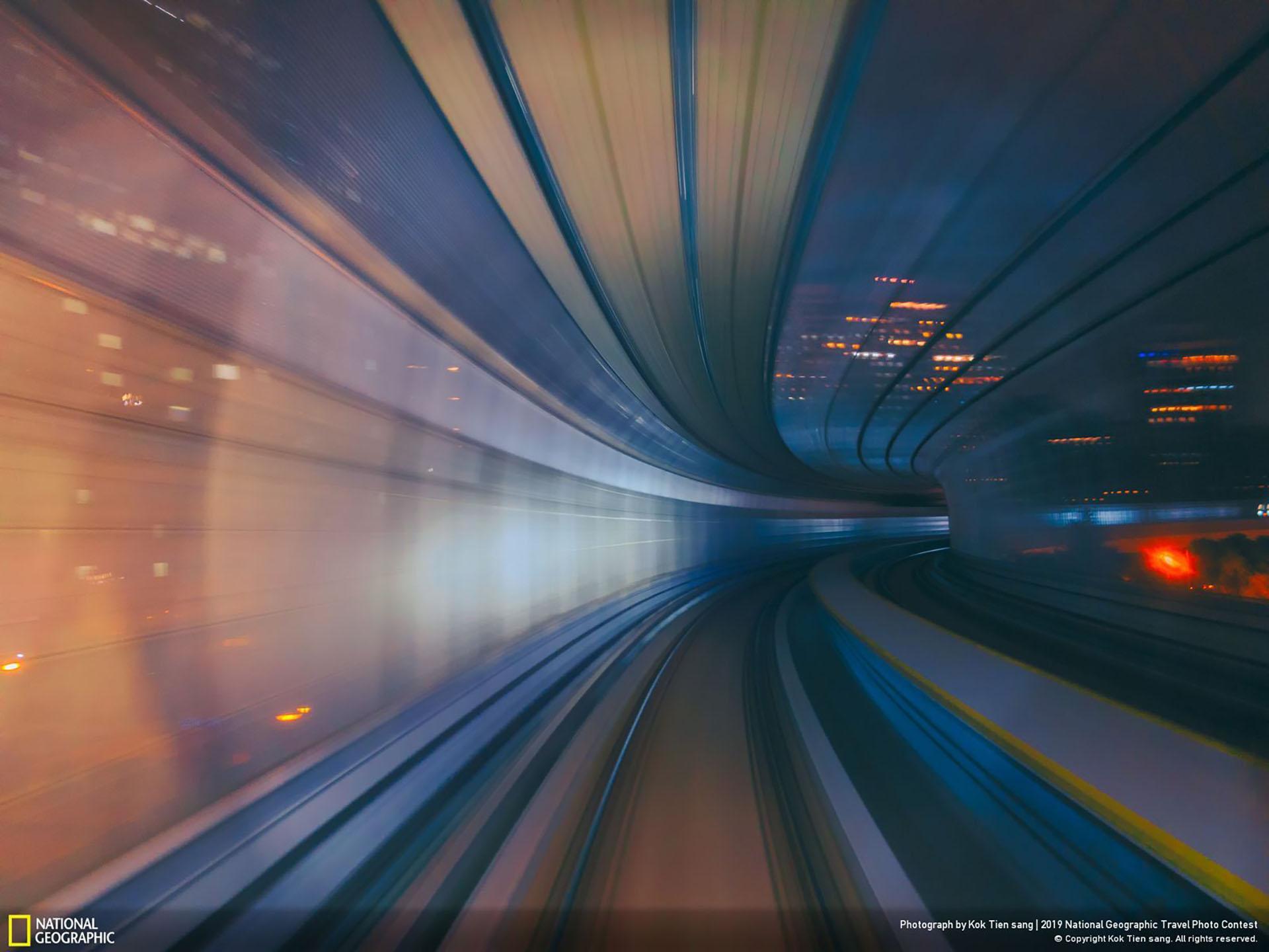 """""""Viaje en el tiempo"""", por Kok Tien Sang: """"Usando mi teléfono para capturar el movimiento del tren cuando este pasa por un túnel. Siento que estoy viajando a través de un túnel del tiempo hacia otra dimensión"""". (""""Time Travel"""" / 2019 National Geographic Travel Photo Contest / Categoría: Ciudades / Ubicación: Kuala Lumpur, Malasia)"""