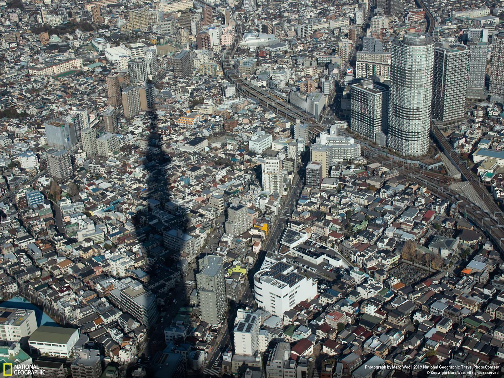 """""""Bajo el Skytree"""", por Marc Woo: """"Estaba en la terraza superior del Skytree alrededor del mediodía, cuando miré hacia afuera, noté que la sombra del Skytree y la calle se intersecaban como las manecillas de un reloj. También me sorprendió la cantidad de hogares que hay debajo del Skytree"""". (""""Under the Skytree / 2019 National Geographic Travel Photo Contest / Categoría: Ciudades / Ubicación: Sumidacho, Tokio, Japón)"""