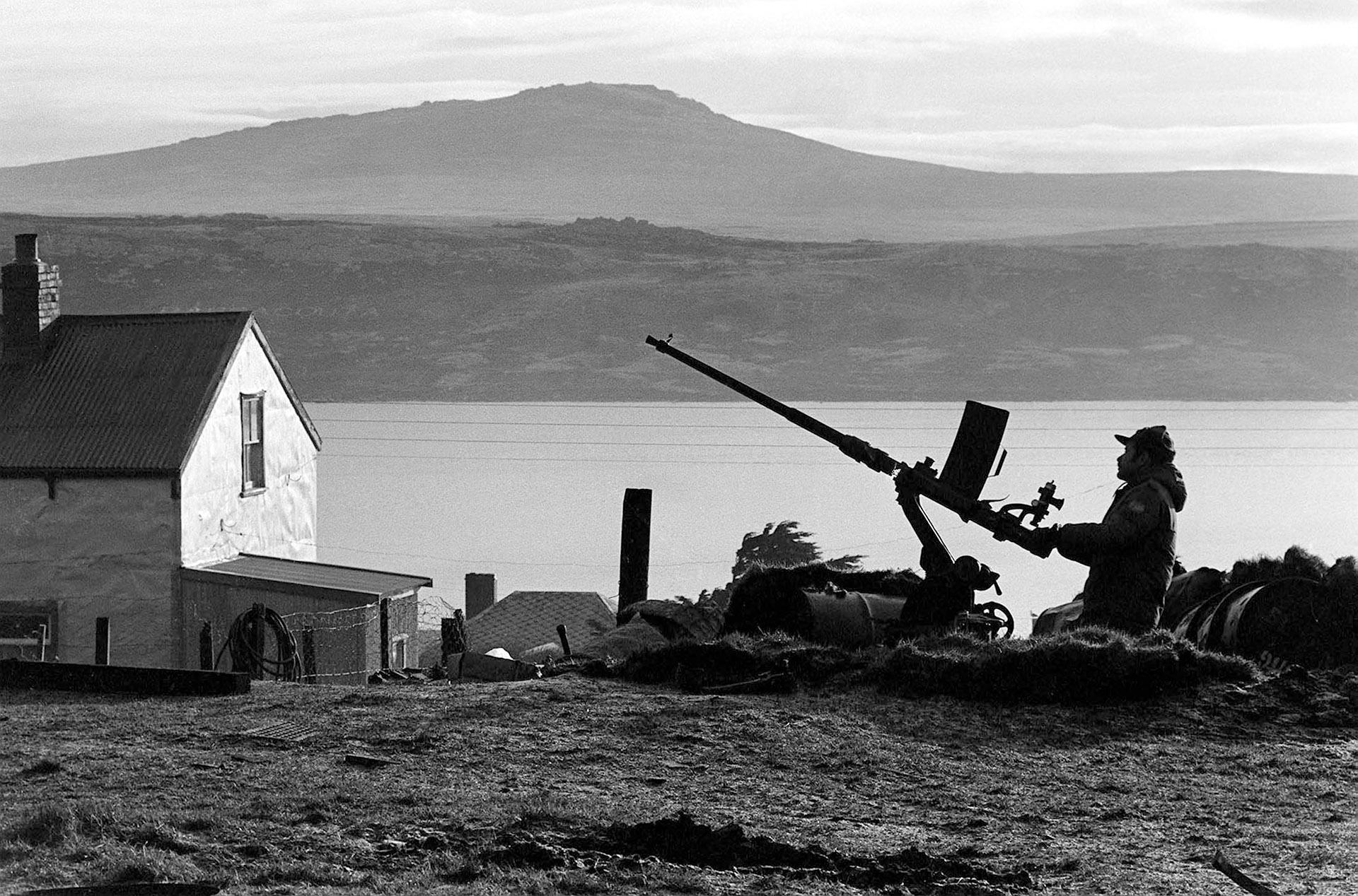 Está solo y espera. Lo acompañan una ametralladora antiaérea y un singular paisaje. La bahía está en calma. Los Harrier no tardarán en llegar. (Foto:Télam)