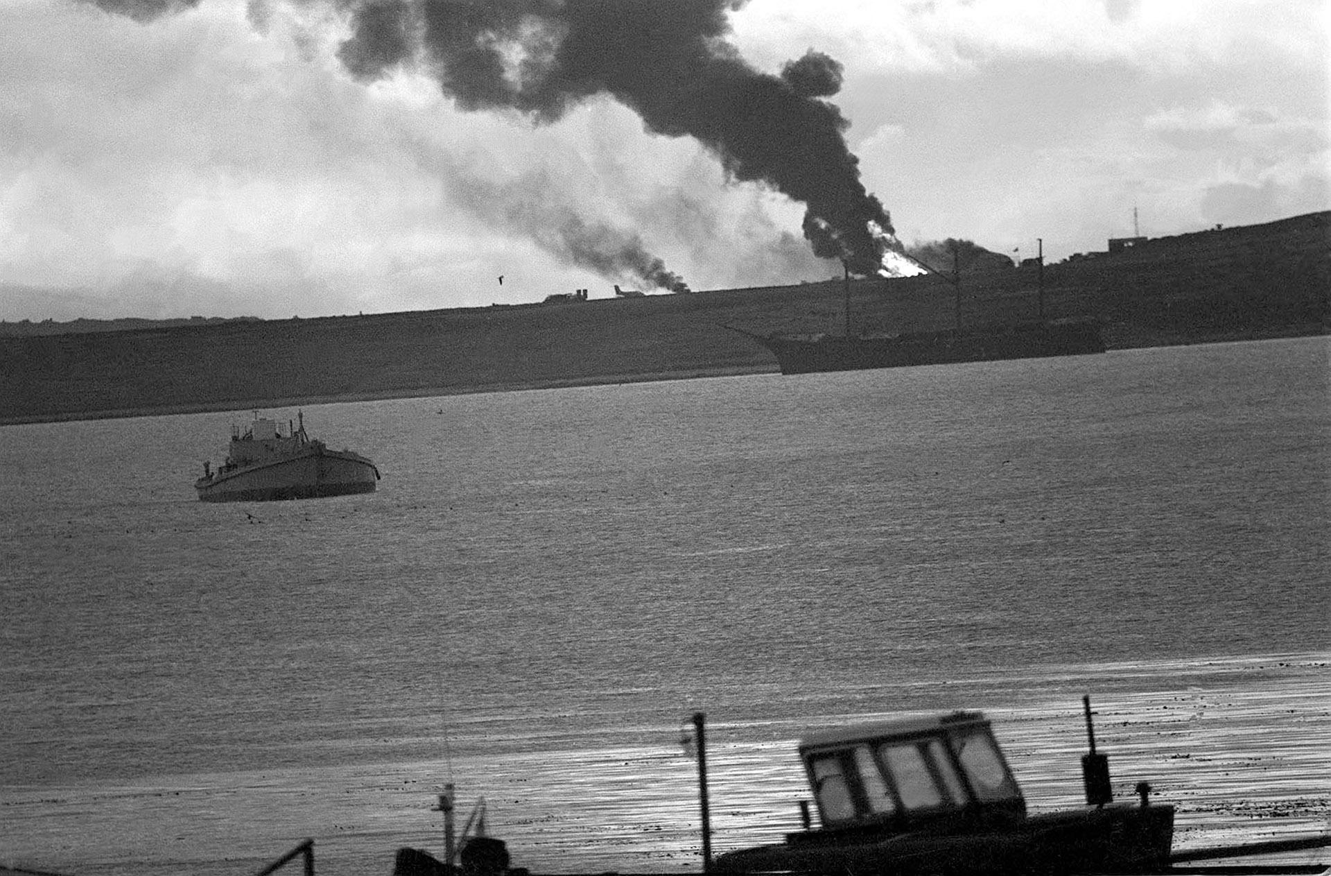 El fuego y el humo caen sobre la bahía. Las bombas inglesas buscaron destruir la pista del aeródromo. A lo lejos, un Pucará permanece ileso a sus efectos. La guerra mostraba su peor cara (Foto: Telam / Román von Eckstein)
